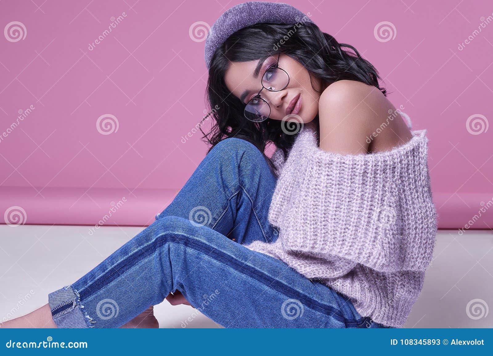 Muchacha asiática encantadora hermosa en suéter púrpura en fondo rosado brillante