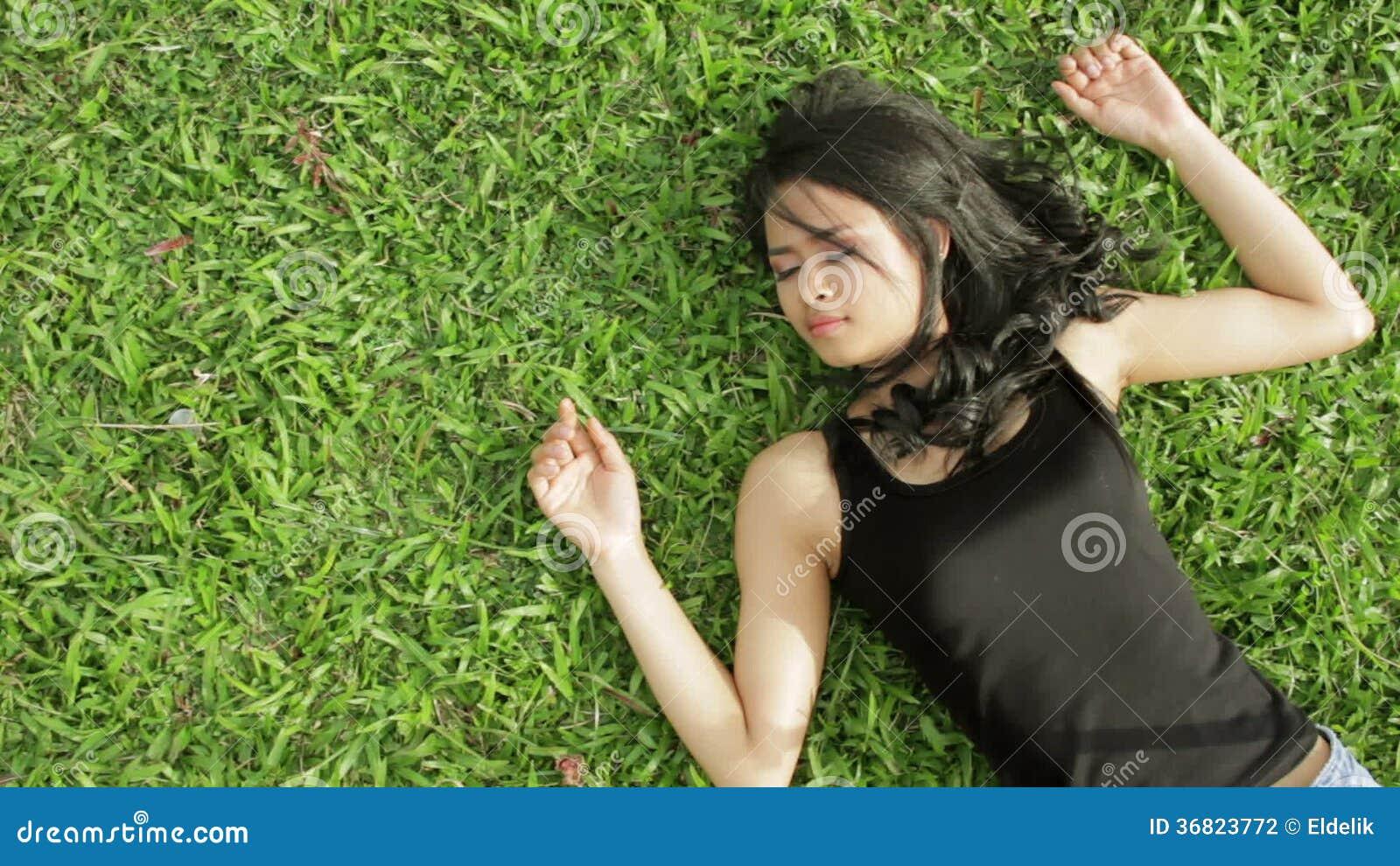 5f5138560 Muchacha asiática erótica atractiva con la mini falda en hierba verde.  Magnífico, adulto.