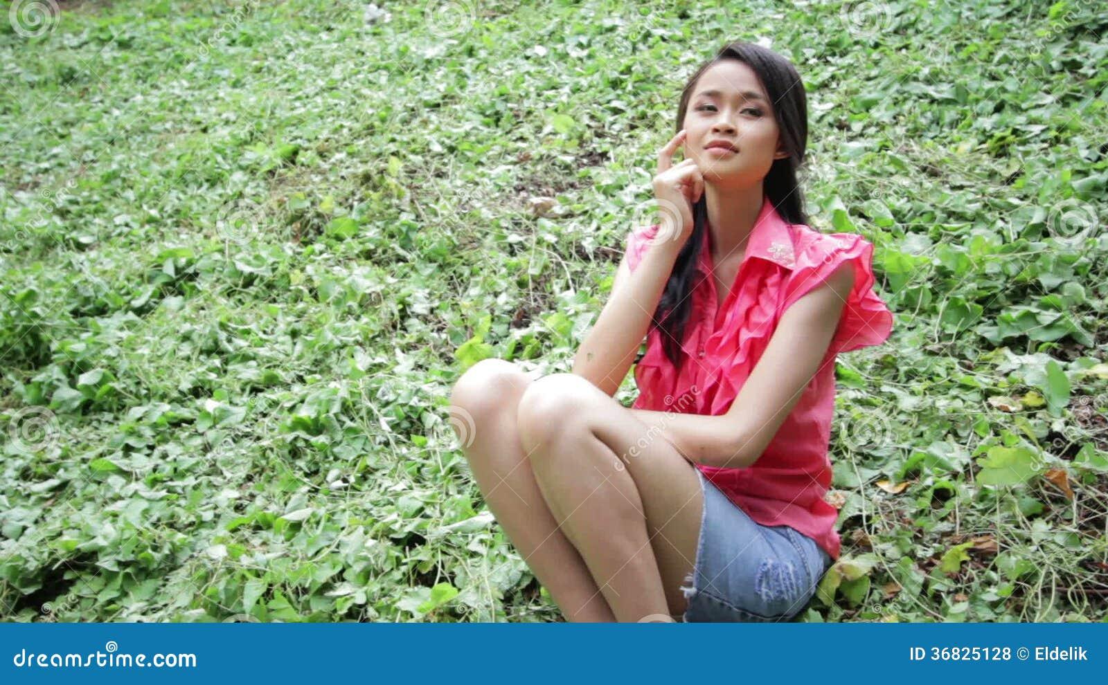 d7f030d65 Muchacha asiática erótica atractiva con la mini falda en hierba verde.  Jardín, asiático.
