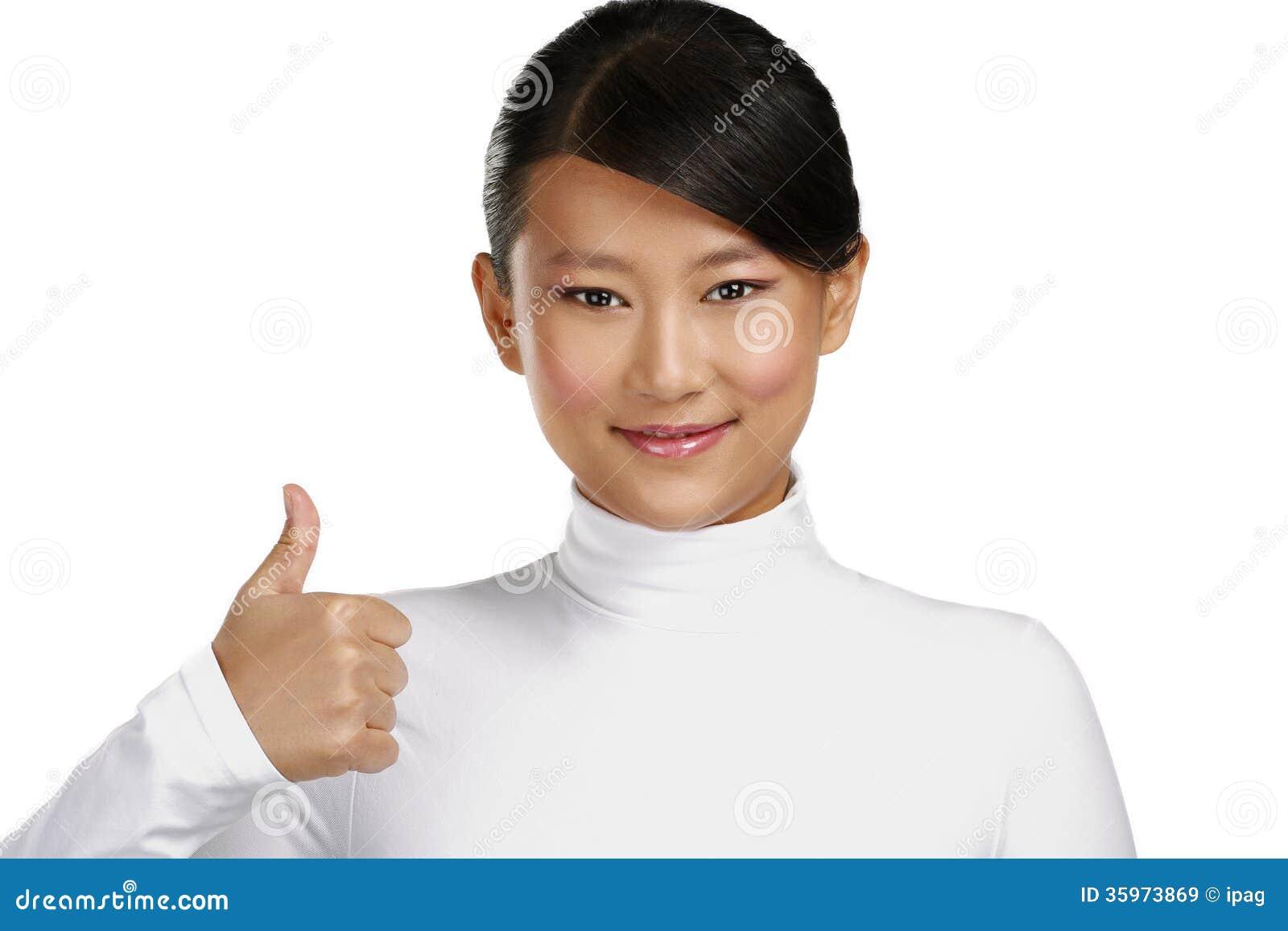 Muchacha asiática feliz hermosa que muestra los pulgares para arriba