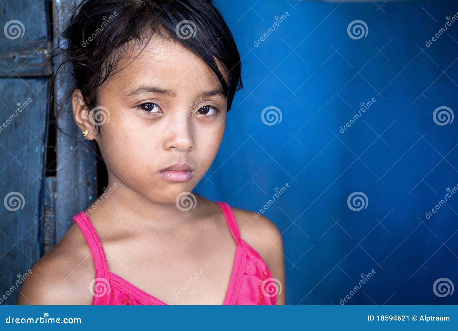 Muchacha asiática joven en pobreza sobre azul