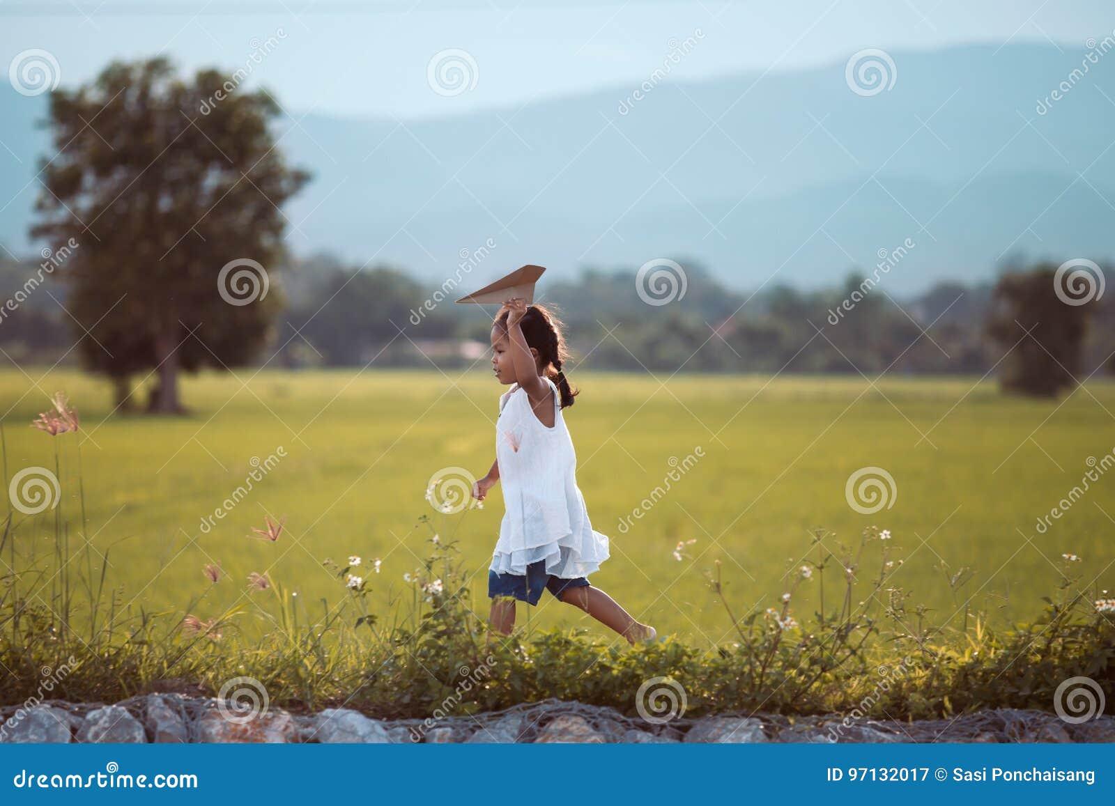 Muchacha asiática linda del niño que funciona con y que juega el aeroplano de papel del juguete
