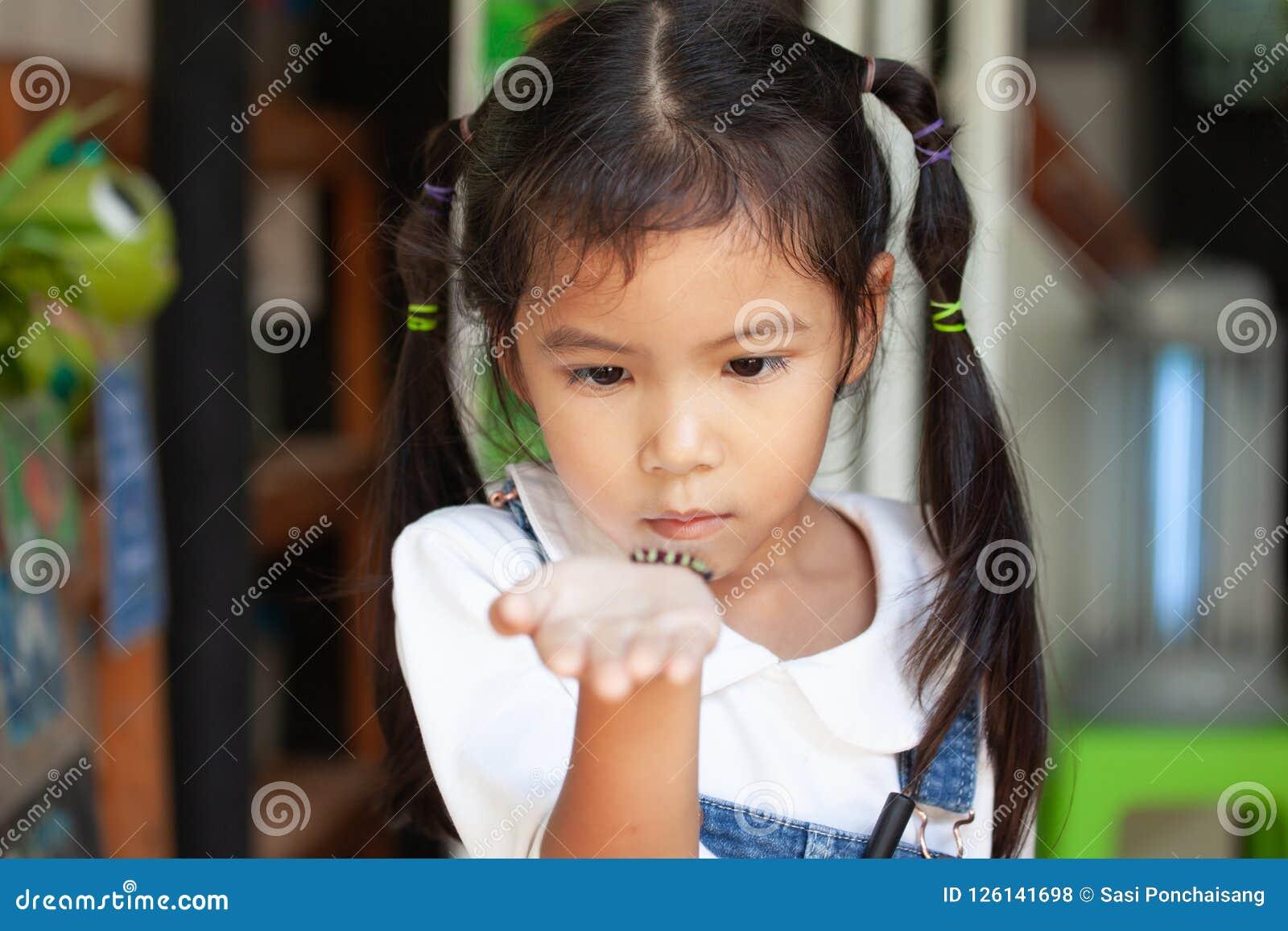 Muchacha asiática linda del niño que se sostiene y que juega con la oruga negra