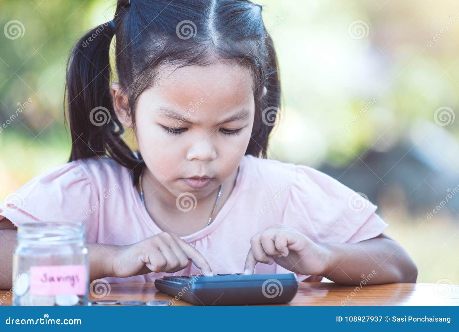 Muchacha asiática linda del pequeño niño que usa la calculadora