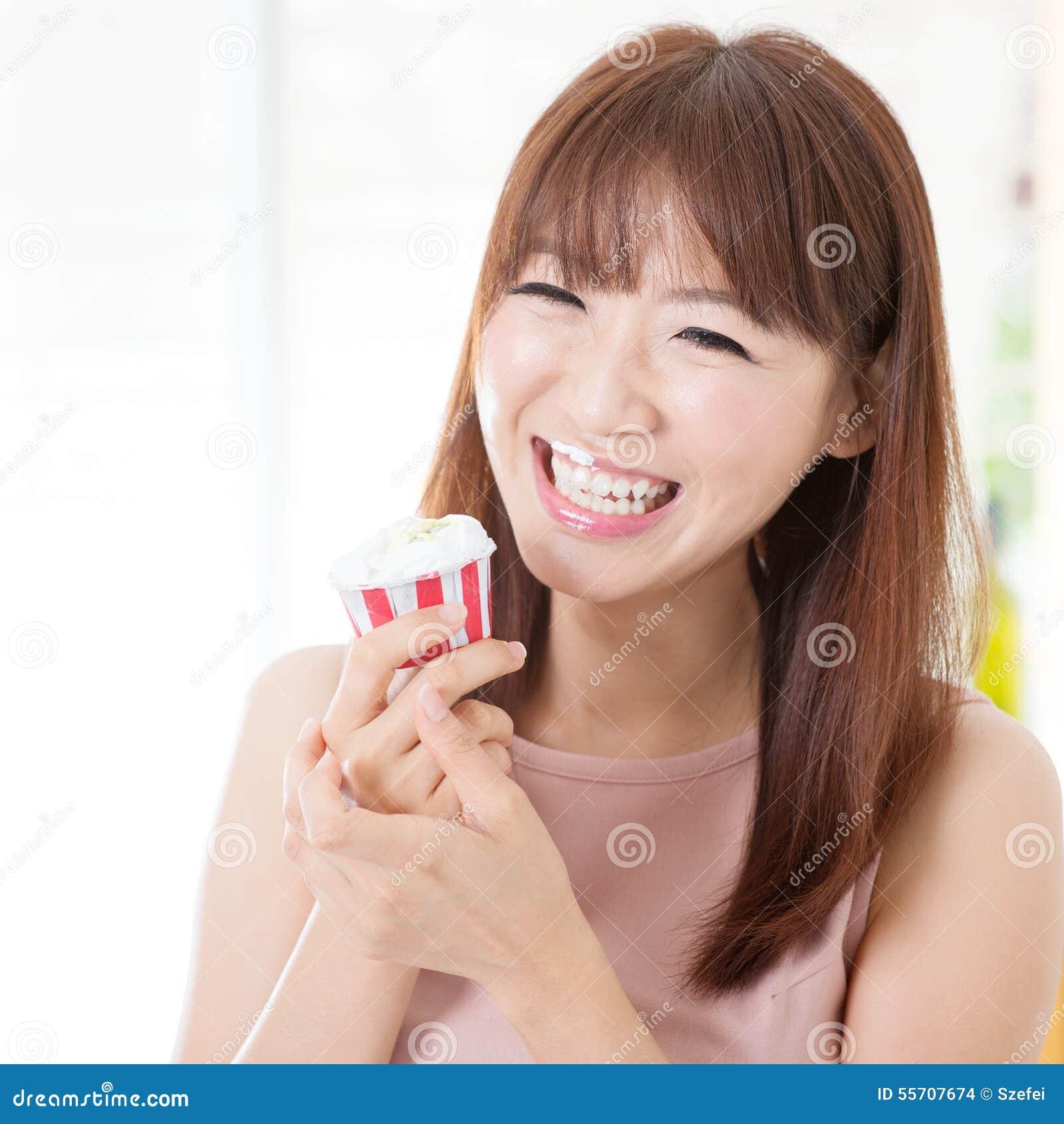 Muchacha asiática que come la magdalena