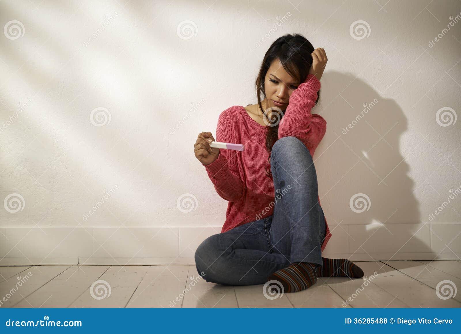 Muchacha asiática triste que mira la prueba de embarazo que se sienta en piso
