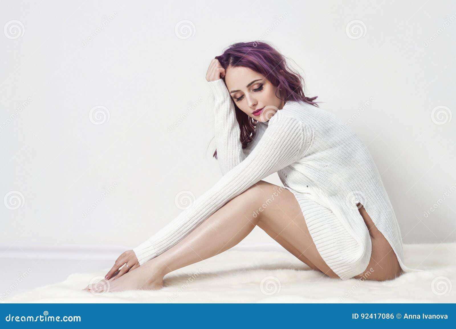 Muchacha atractiva con el pelo púrpura y tatuajes en su cuerpo que presenta en la camisa blanca en fondo gris Mujer perfecta en l
