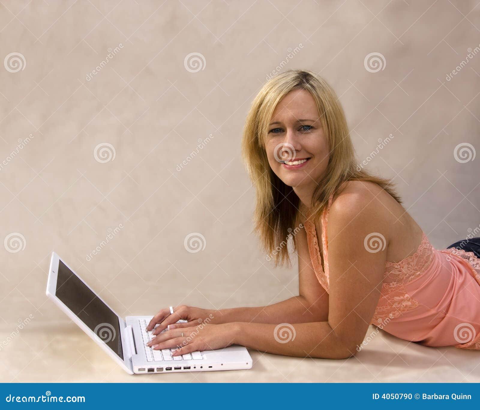 Muchacha atractiva en la computadora portátil