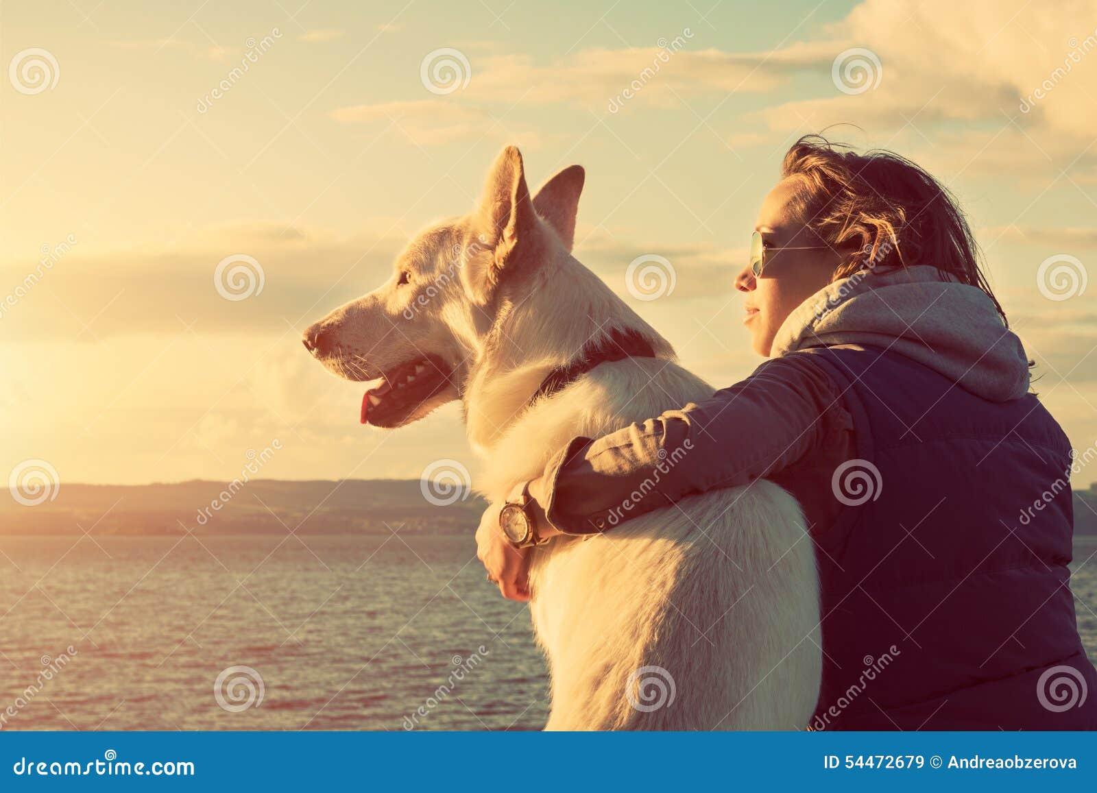 Muchacha atractiva joven con su perro casero en una playa