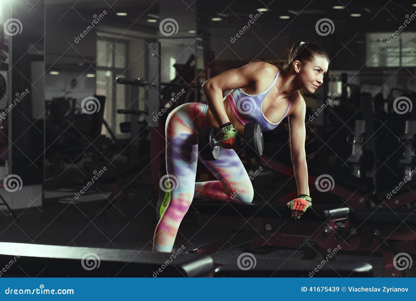 Muchacha atractiva joven de la aptitud en el entrenamiento del gimnasio