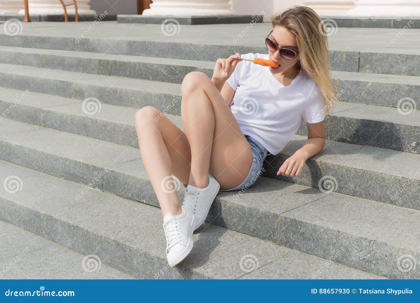 Muchacha atractiva joven hermosa en gafas de sol que come el helado en la escalera y que lame los labios regordetes al día calien