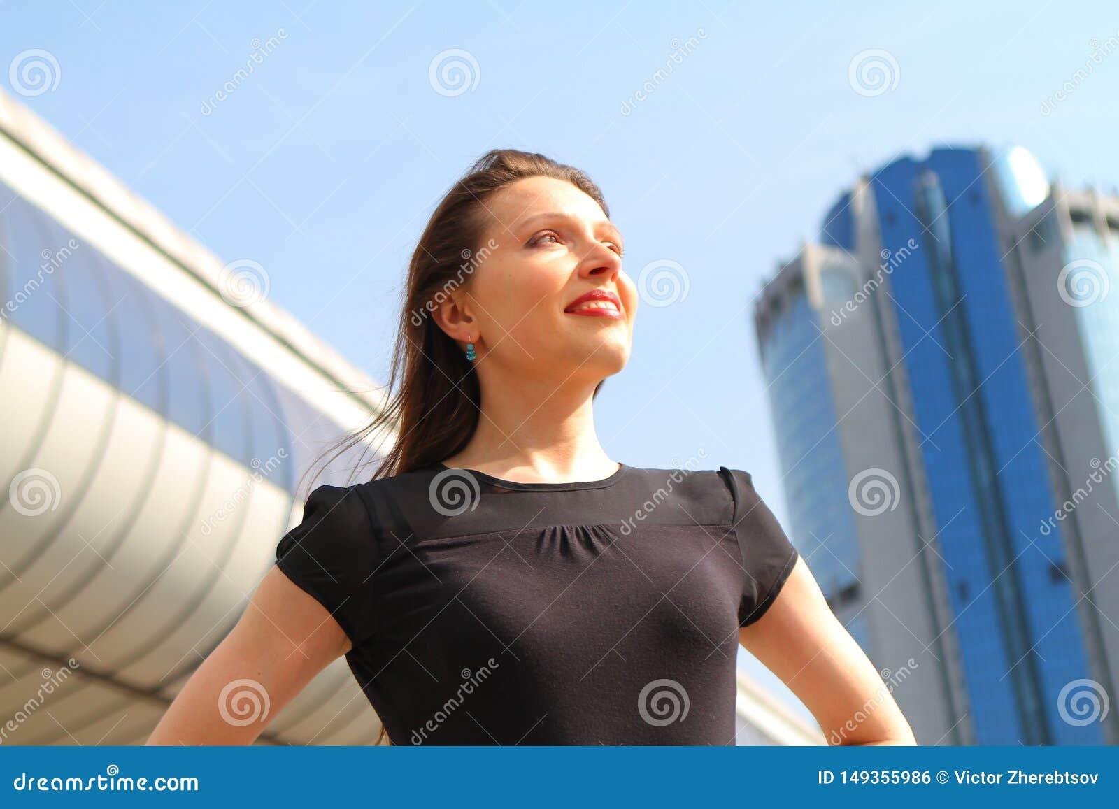 Muchacha atractiva joven que sonr?e mirando el cielo