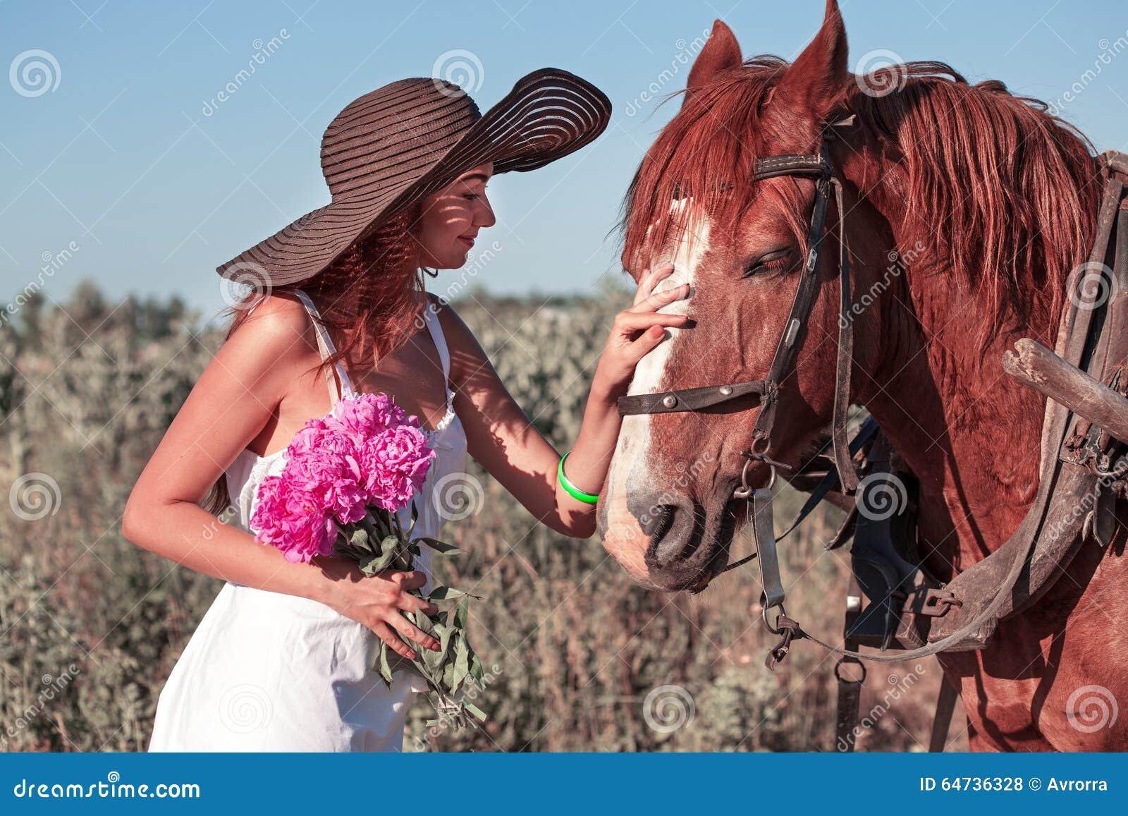 Muchacha bonita con los wildflowers en el carro del caballo en día de verano