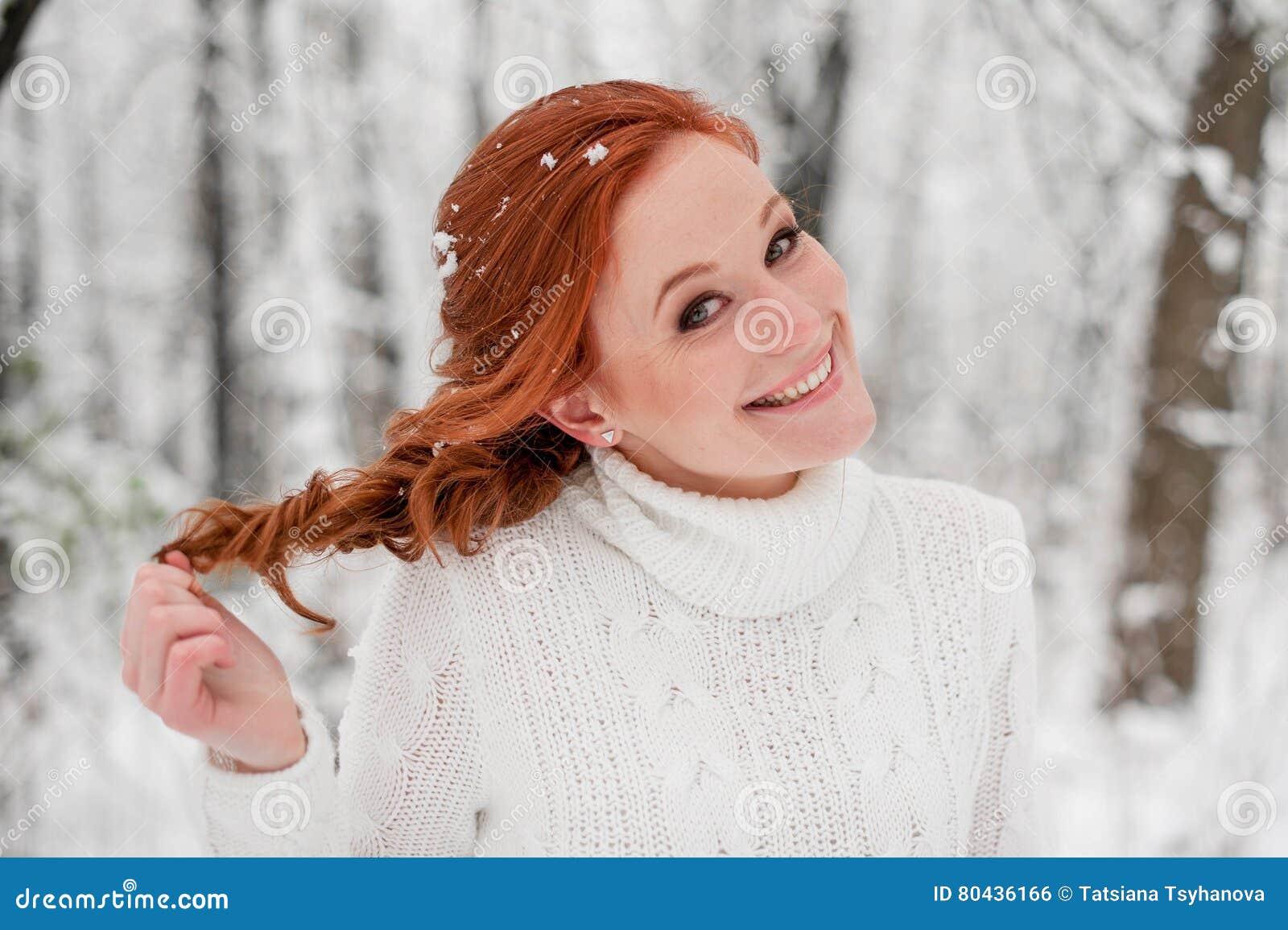 Muchacha bonita del jengibre en el suéter blanco en la nieve diciembre del bosque del invierno en parque Retrato Tiempo lindo de