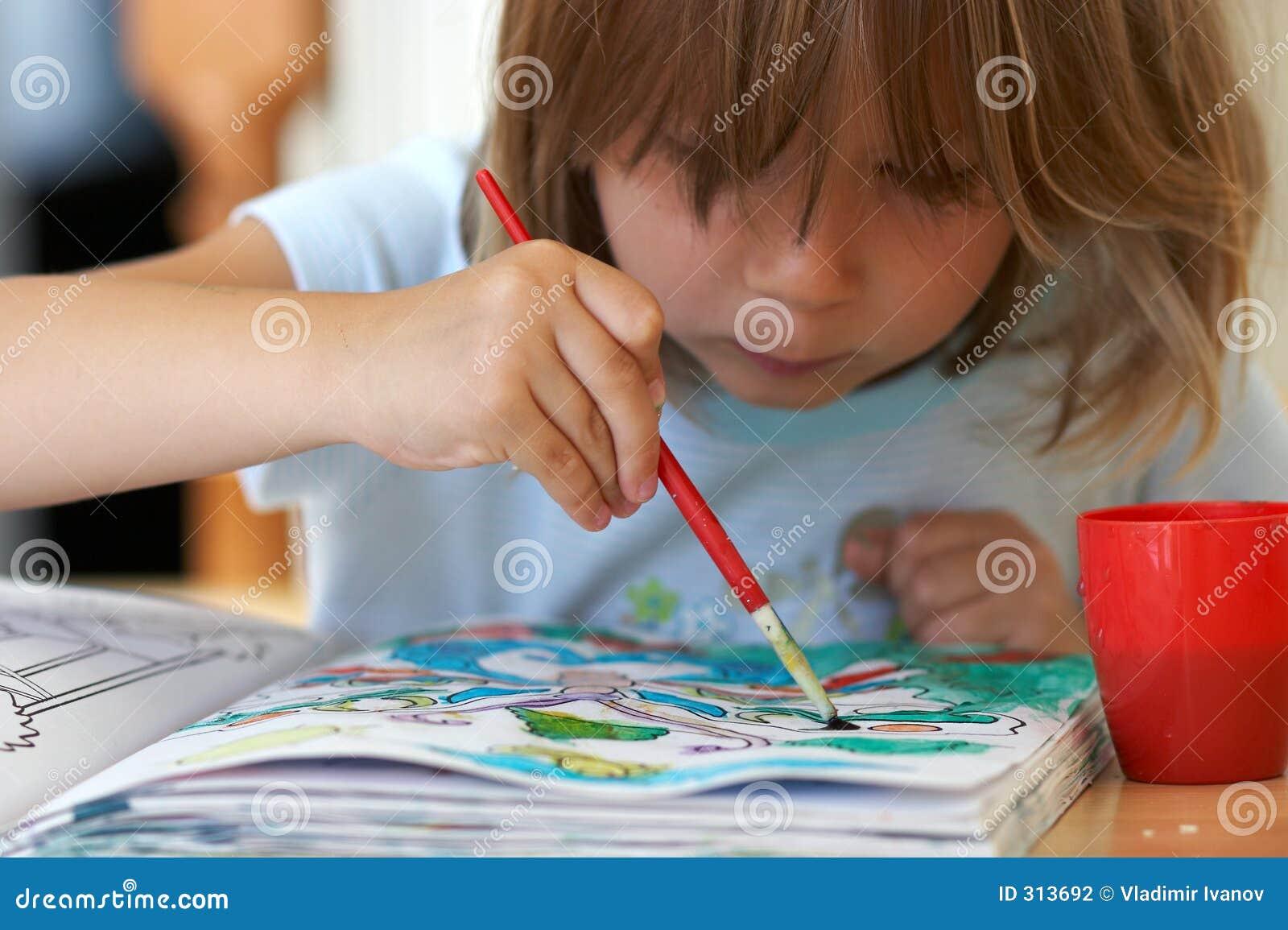 Muchacha bonita que colorea un libro