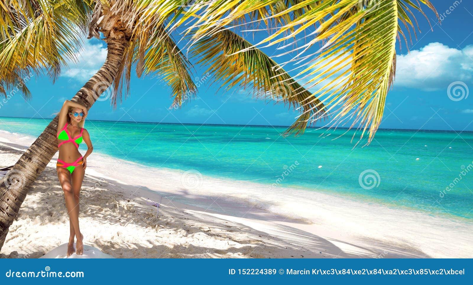 Muchacha bronceada hermosa en soportes de moda del bikini al lado de una palmera en la playa de una isla tropical Vacaciones de v