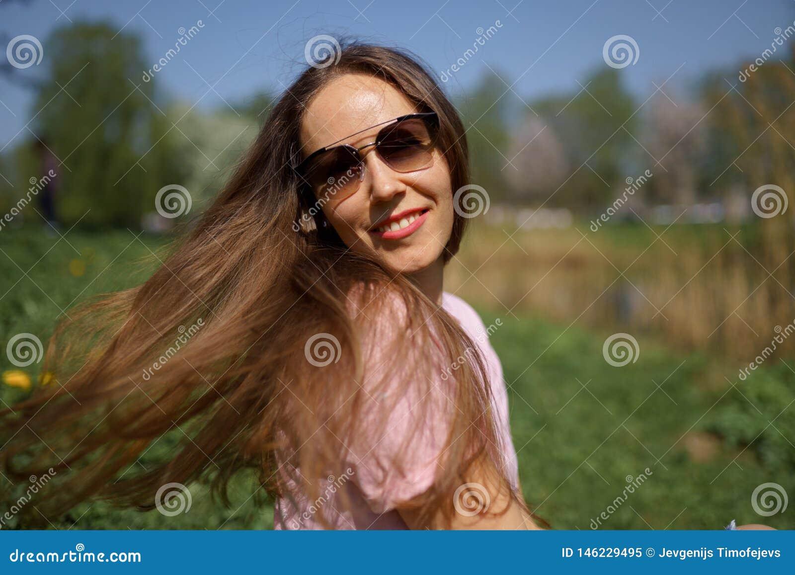 Muchacha cabelluda de la mujer del marr?n feliz joven del viajero que sonr?e y que da vuelta alrededor en un nuevo pa?s de destin