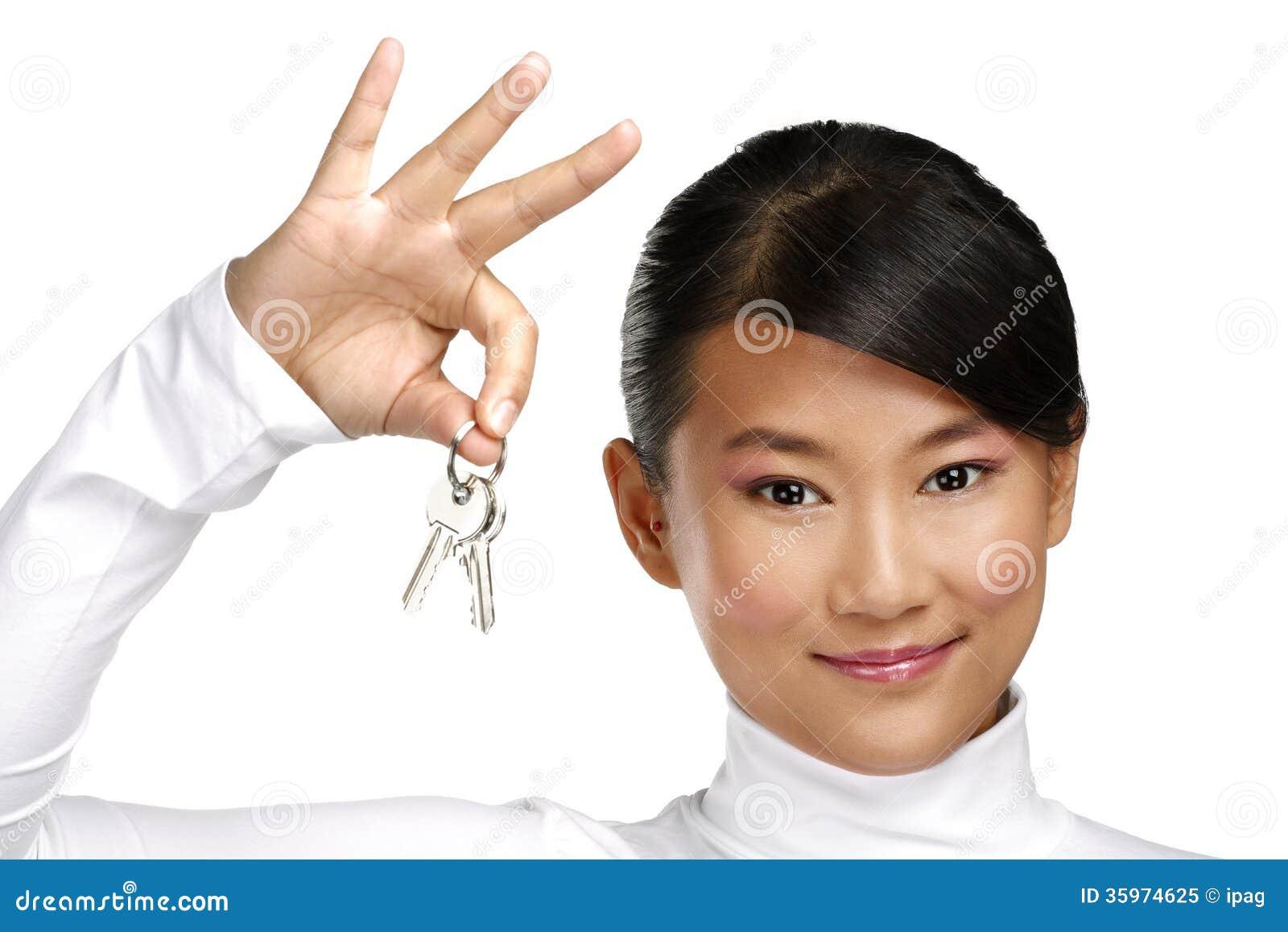 Muchacha china asiática linda que muestra llaves planas