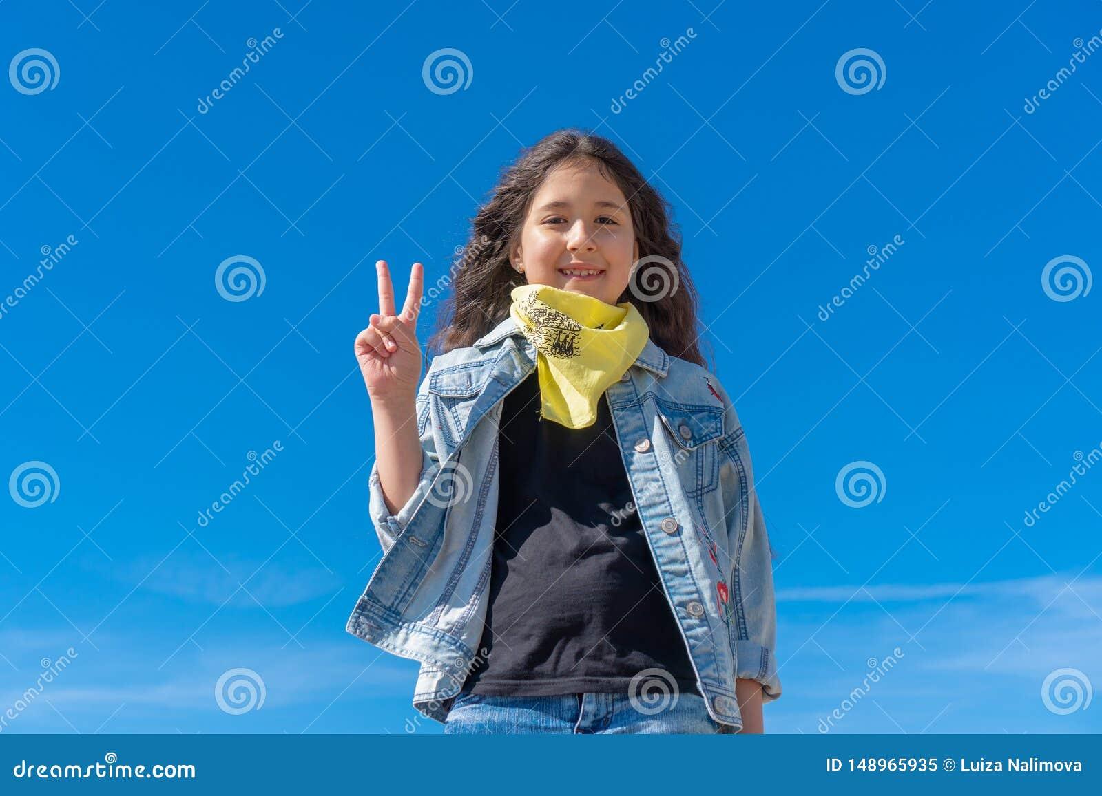 Muchacha con el pelo largo negro contra la mirada sonriente clara del cielo azul a la c?mara que muestra los fingeres que hacen l