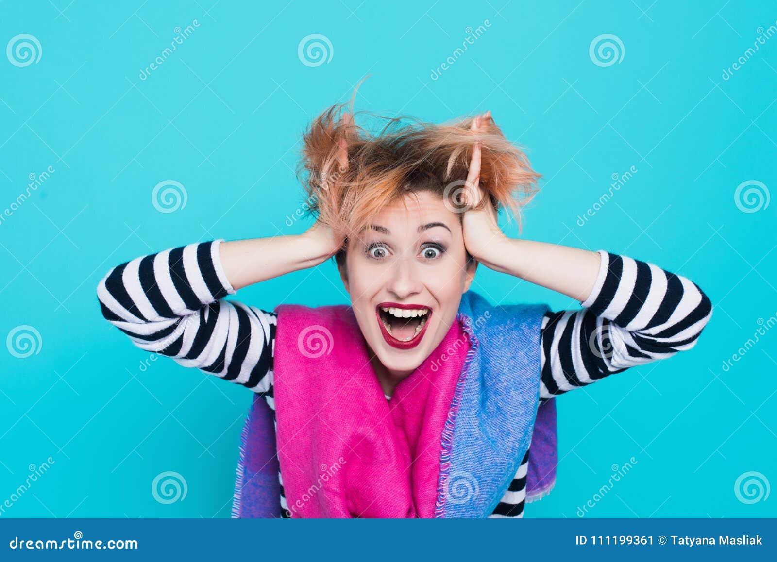 Muchacha con el pelo rojo que ríe llevando a cabo su cabeza Pelo enredado Emociones positivas Tiro del estudio
