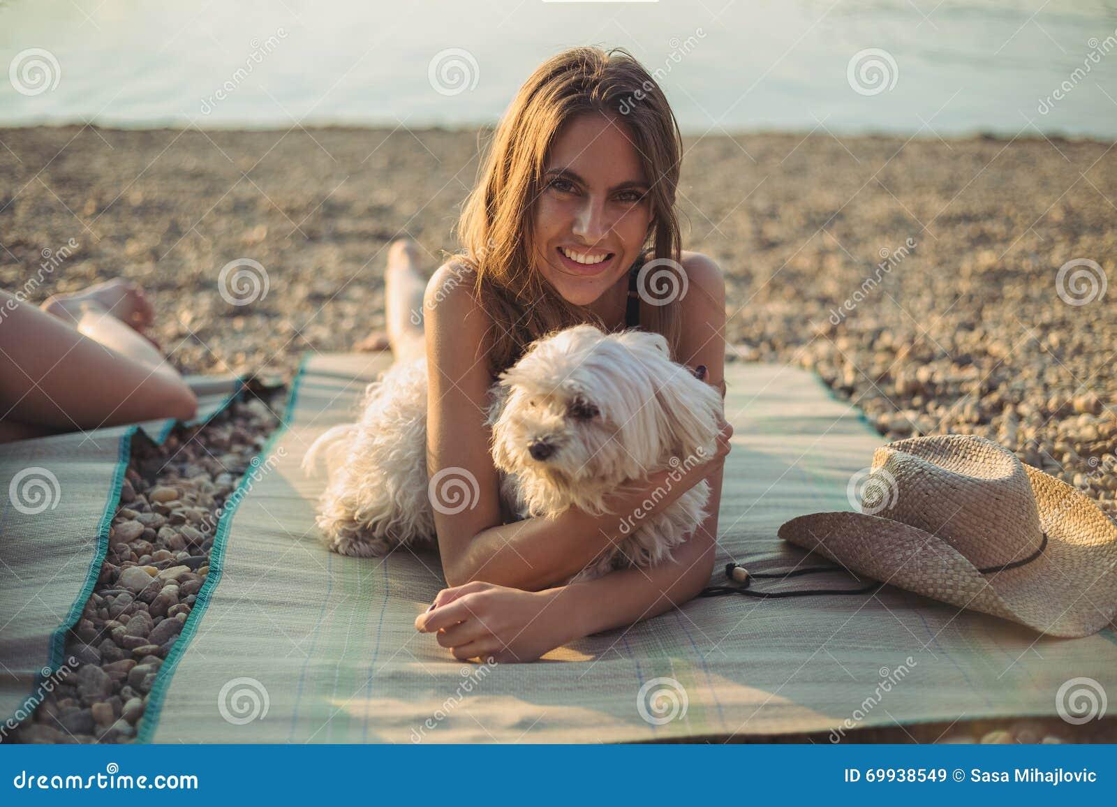 Muchacha con el perro que miente en la playa y la sonrisa