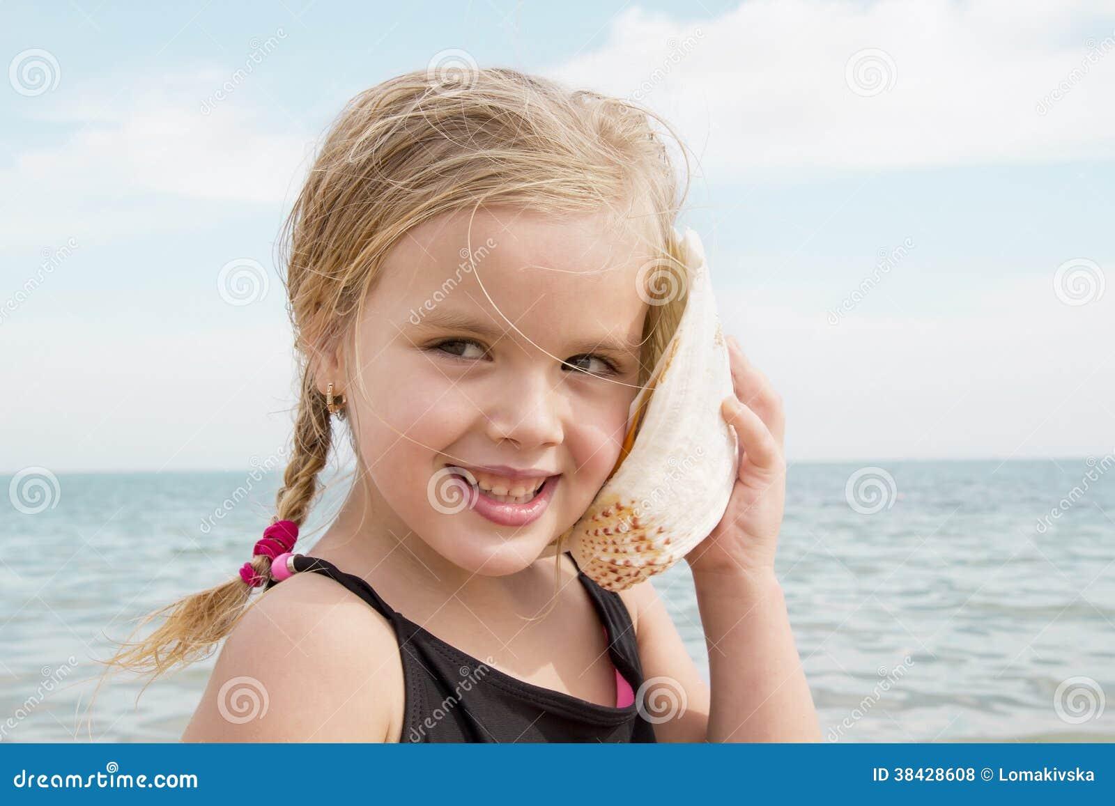Muchacha con la cáscara que escucha el mar