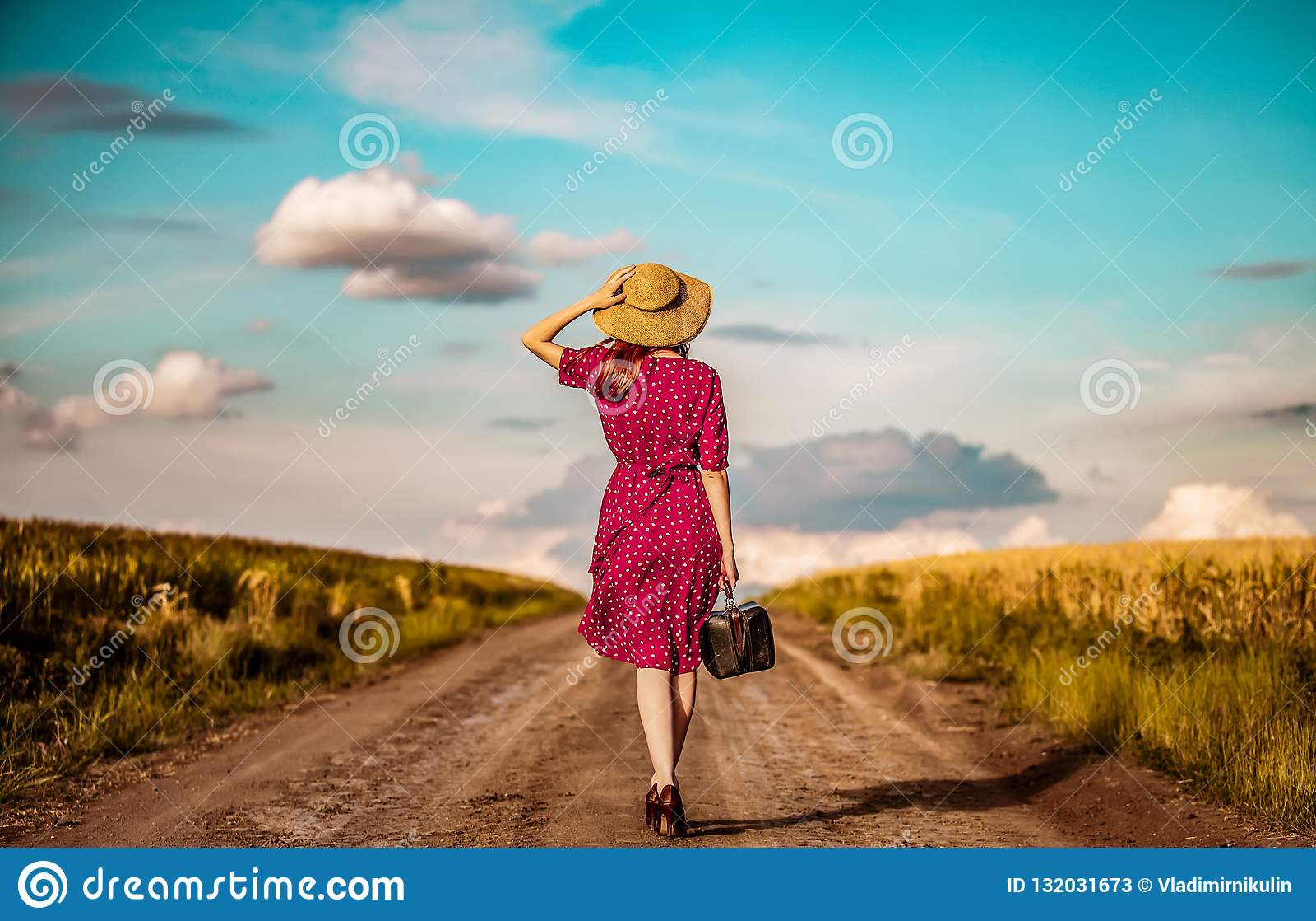 Muchacha con la maleta que despierta en el camino rural