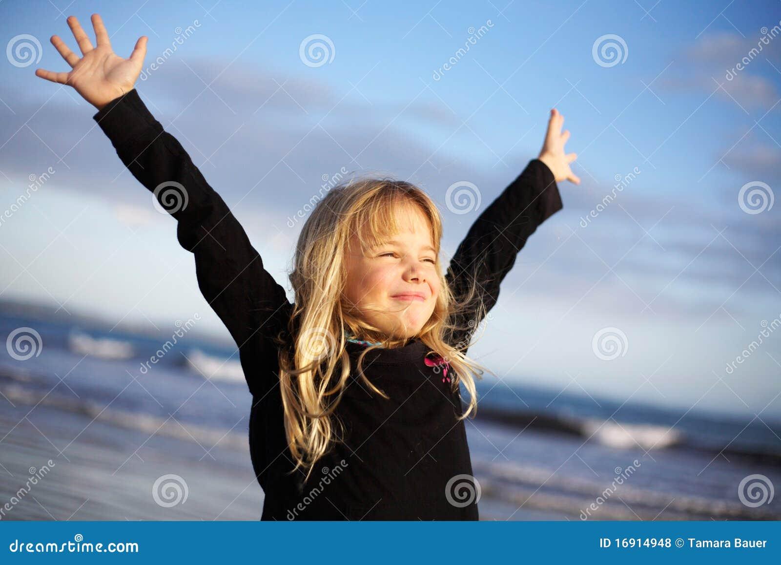 Muchacha con los brazos outstretched en la playa