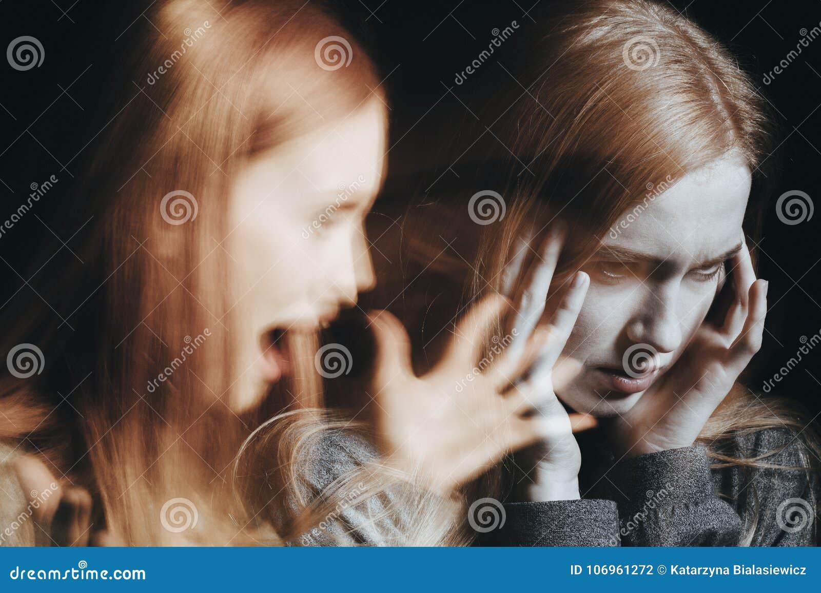 Muchacha con los oídos de la cubierta de la esquizofrenia