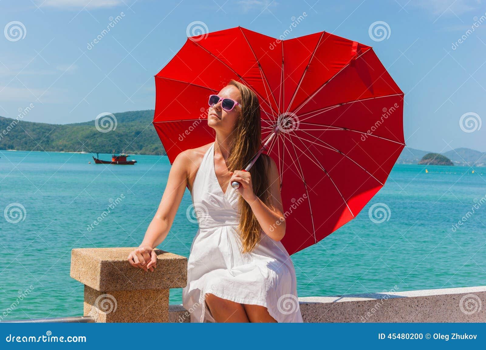 Muchacha con un paraguas contra el mar