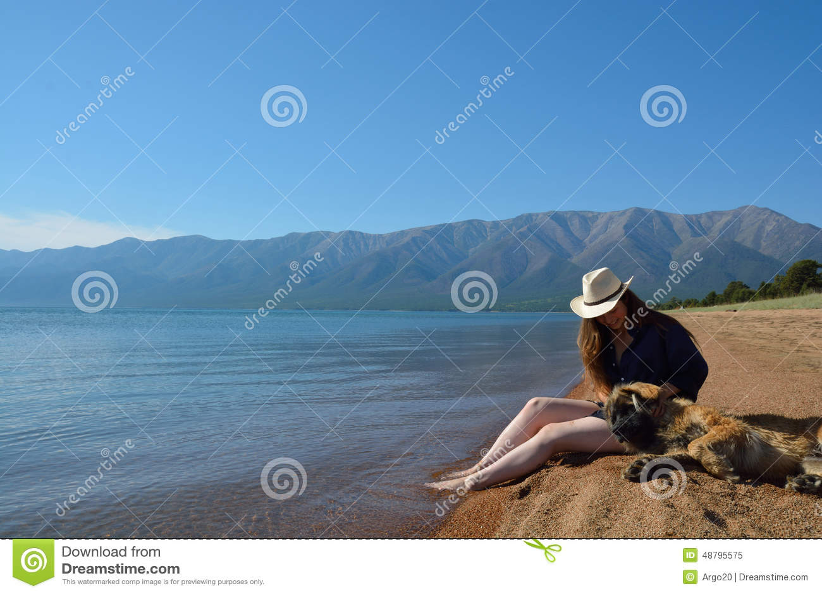 Muchacha con un perro en la orilla del lago Baikal