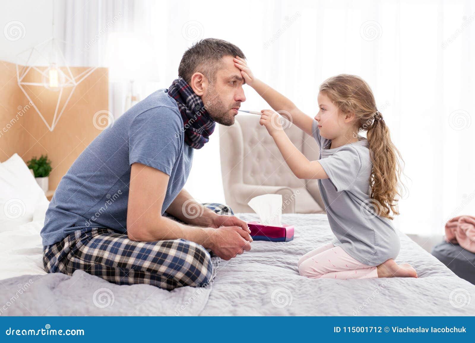 Muchacha concentrada que trata a su padre enfermo
