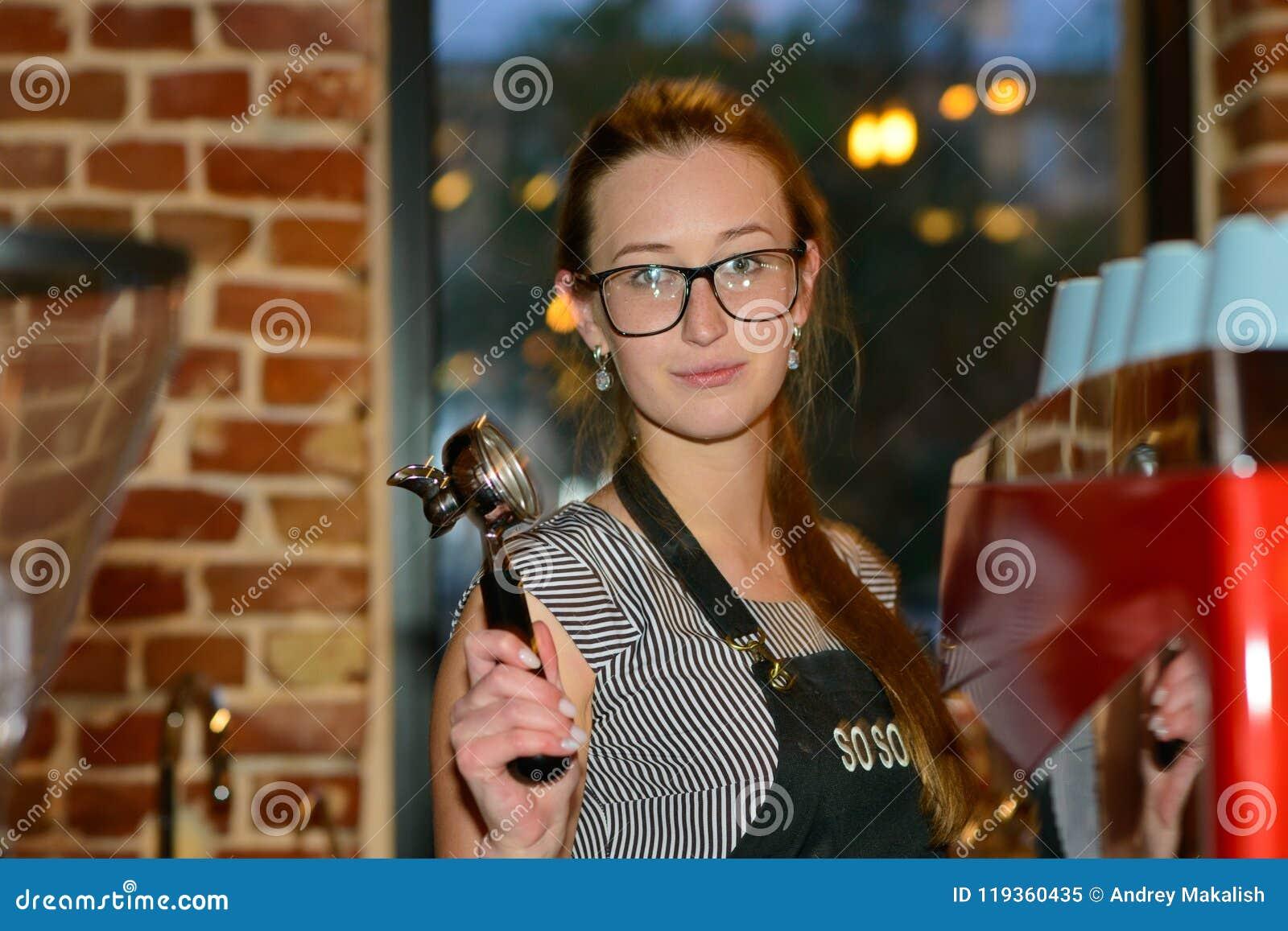 Muchacha de Barista con el receptor a disposición detrás de la barra en el café