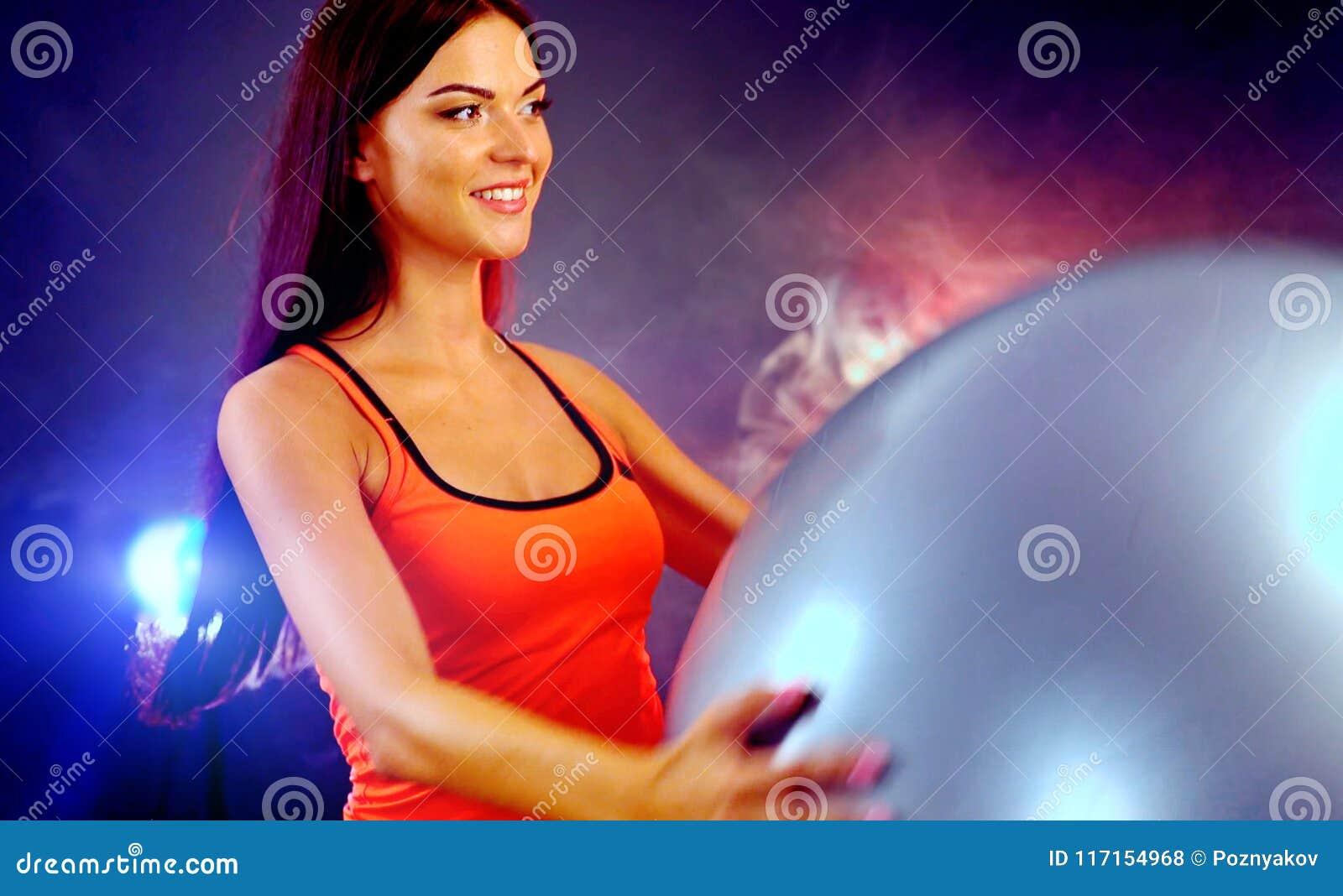 Muchacha de la aptitud que ejercita en gimnasio con el fitball