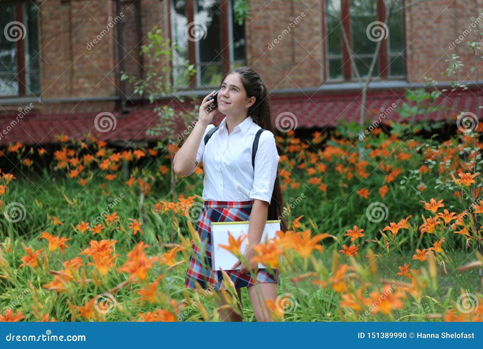 Muchacha de la colegiala con el pelo largo en uniforme escolar que habla en el teléfono