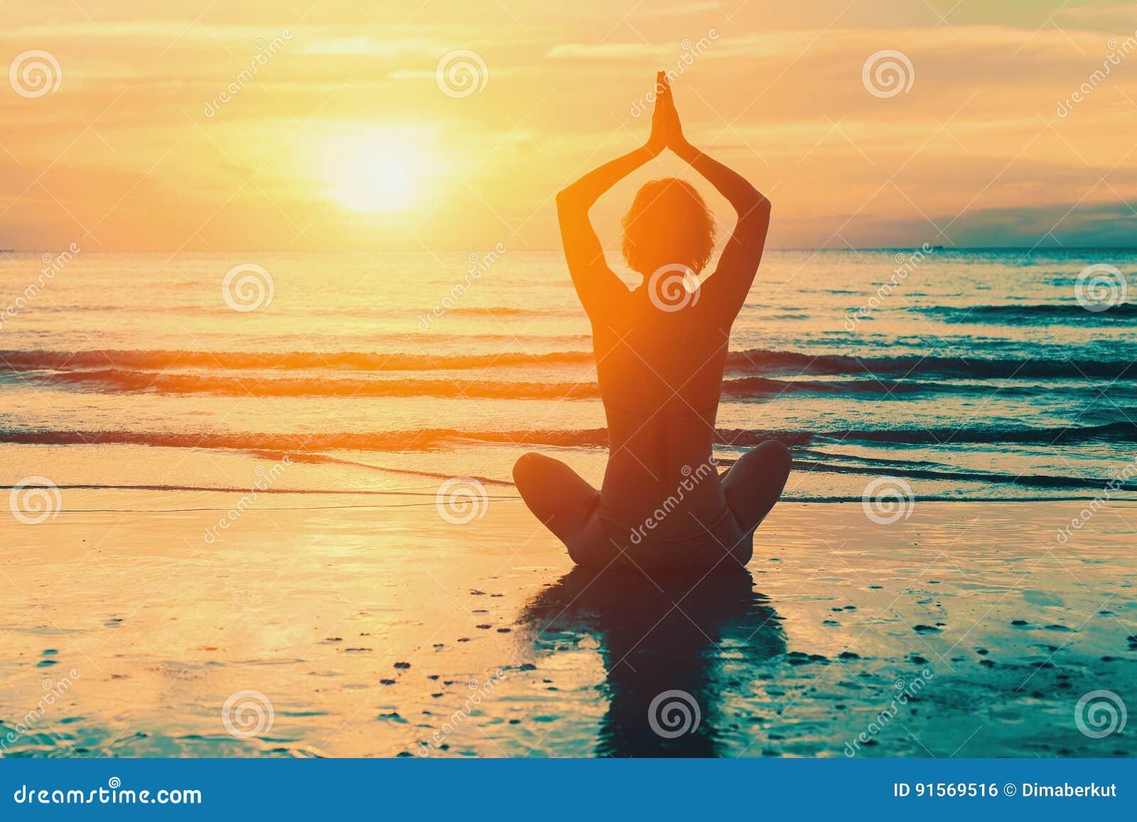 Muchacha de la meditación en el mar durante puesta del sol