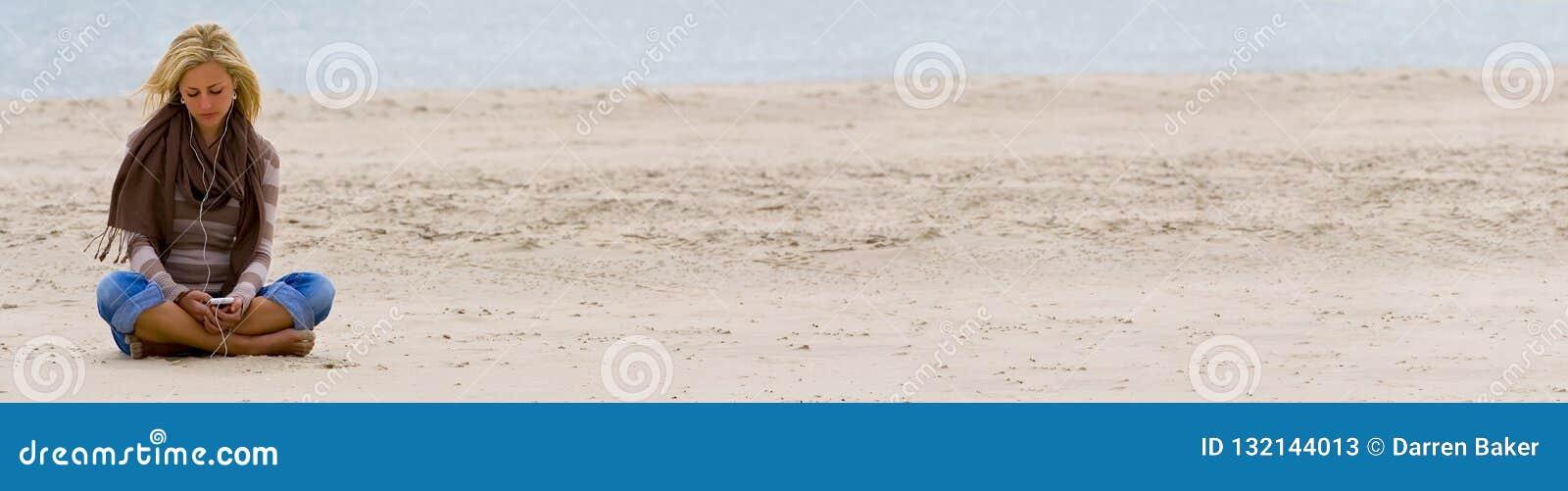 Muchacha de la mujer en la playa que escucha la música en el teléfono elegante