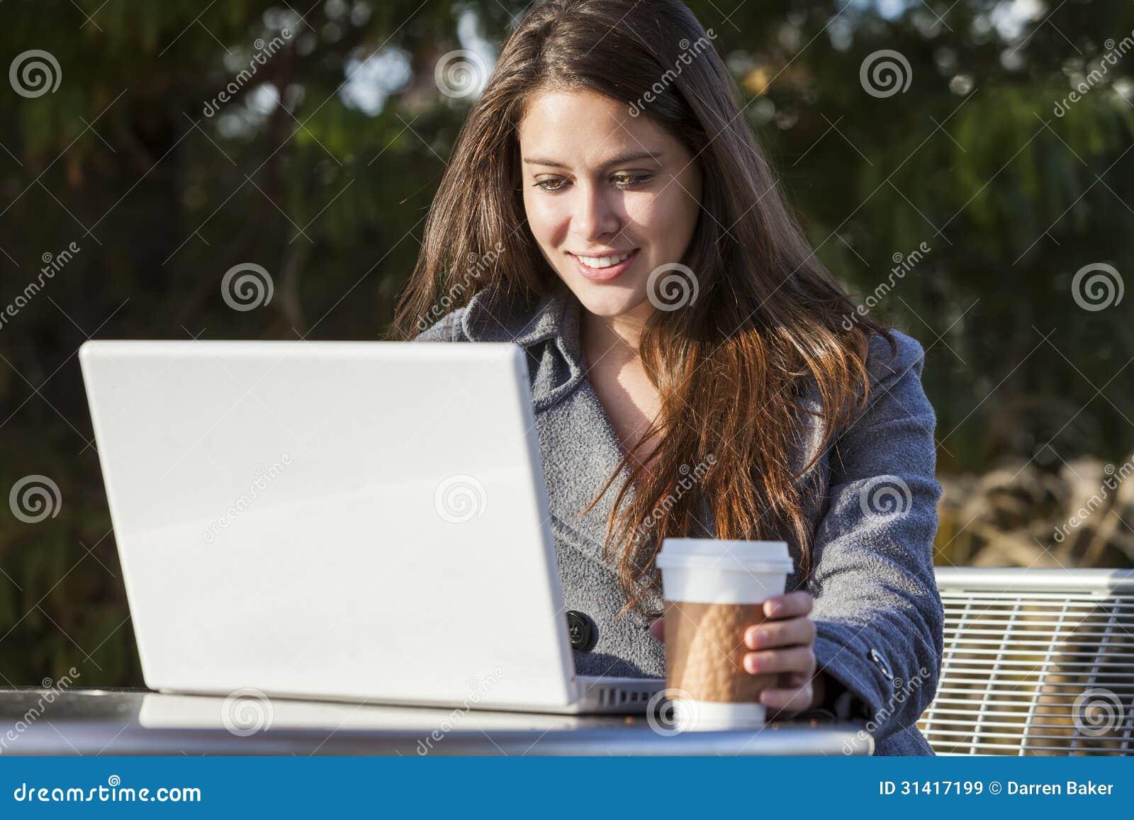 Muchacha de la mujer joven que usa el café de consumición del ordenador portátil