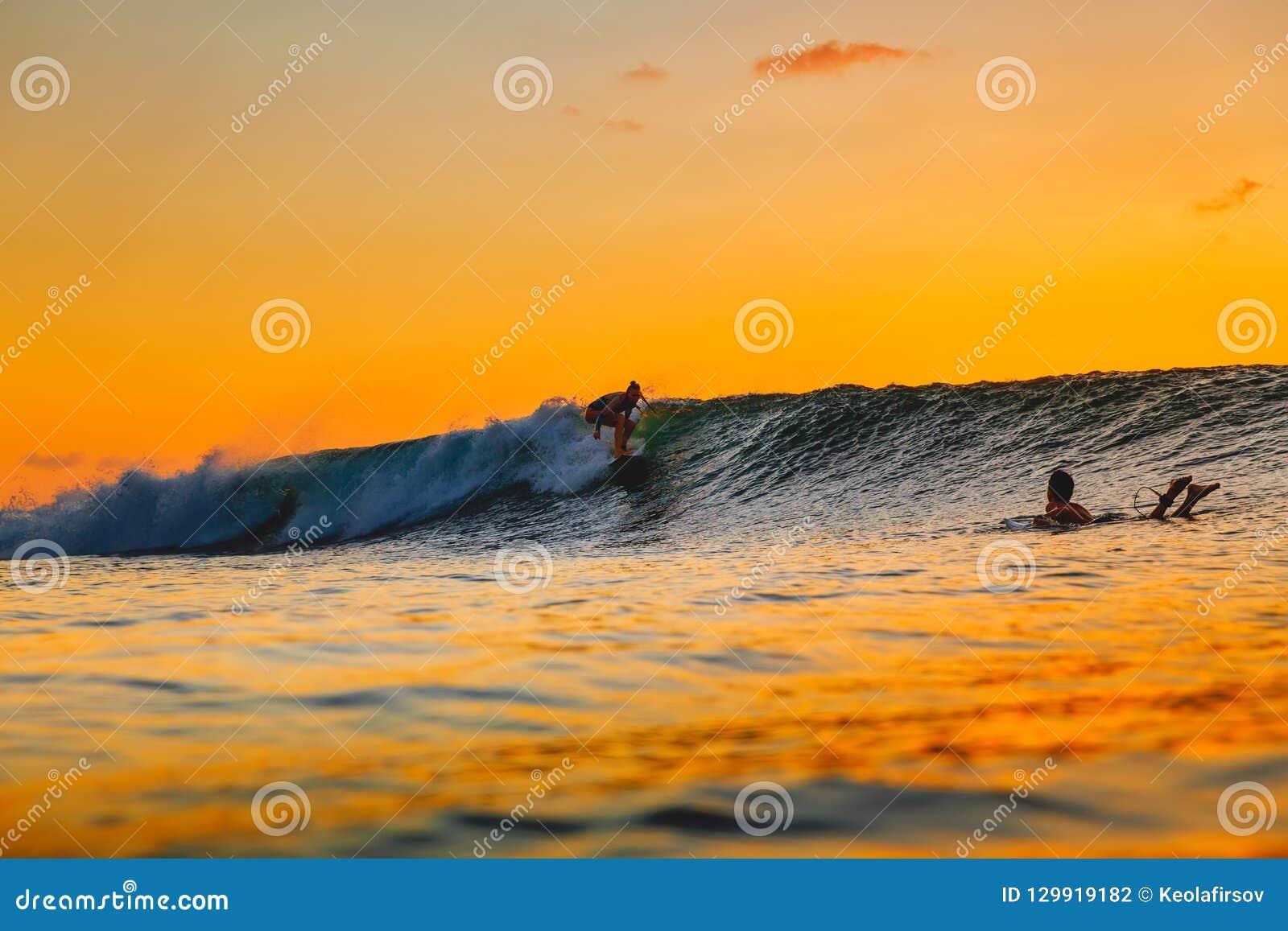 Muchacha de la resaca en la tabla hawaiana en la puesta del sol Mujer en el océano, el practicar surf de la puesta del sol