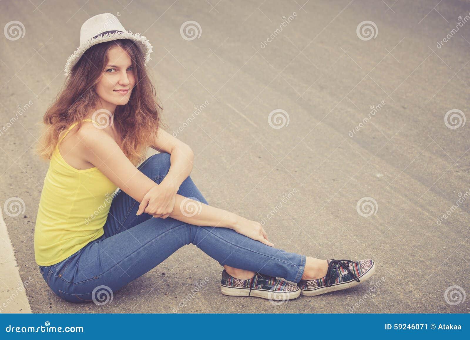 Muchacha de moda del inconformista en el sombrero que se relaja en el camino en el día t