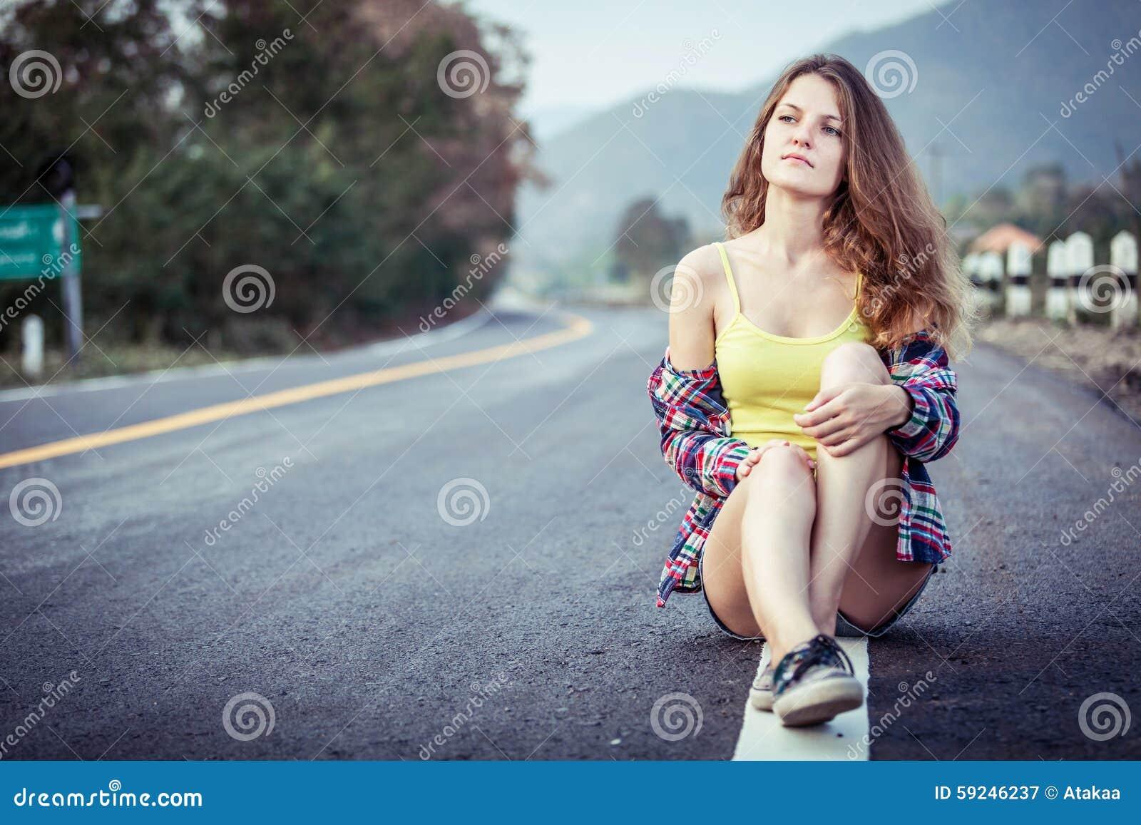 Muchacha de moda del inconformista que se relaja en el camino en el tiempo del día