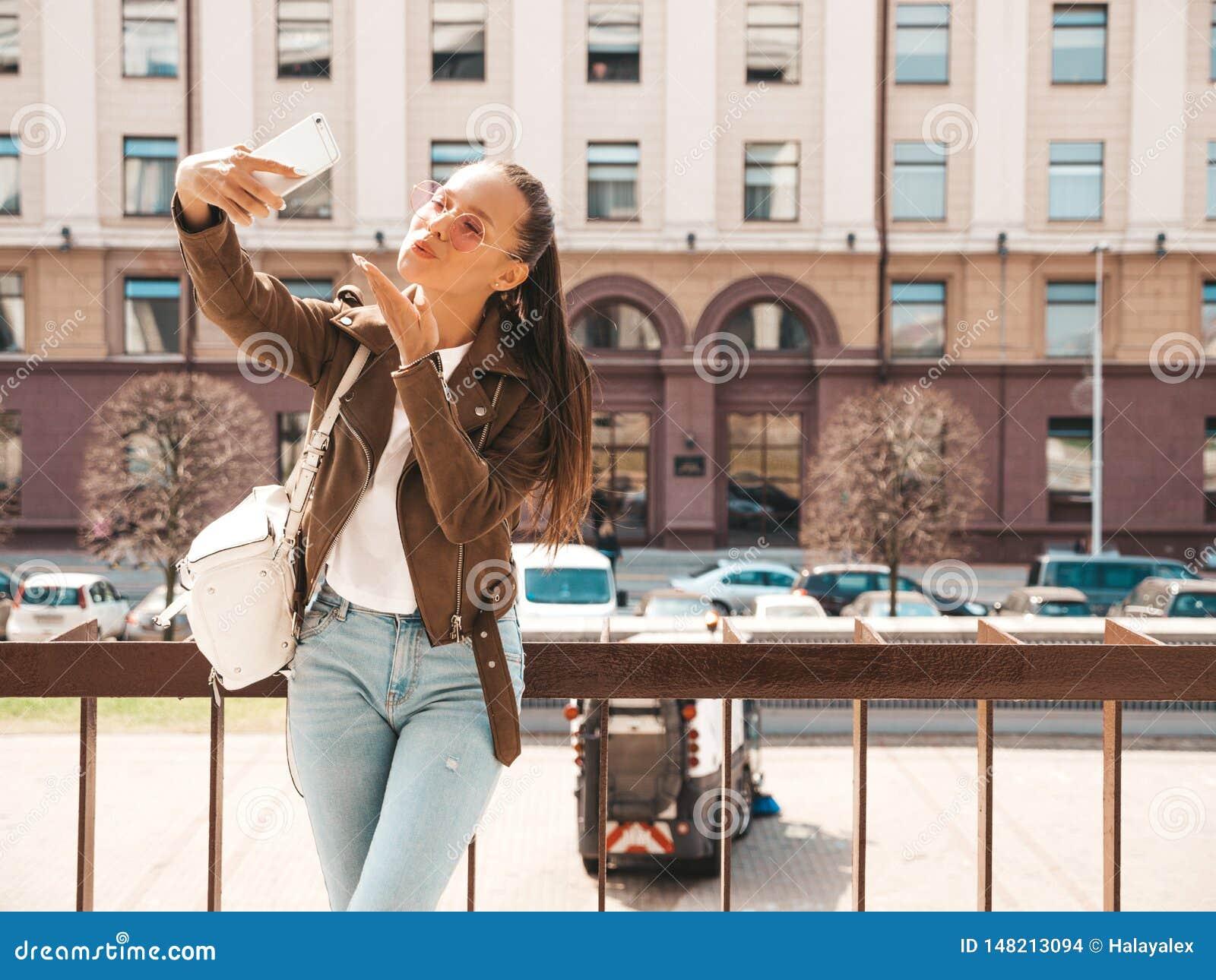 Muchacha de moda hermosa que presenta en la calle