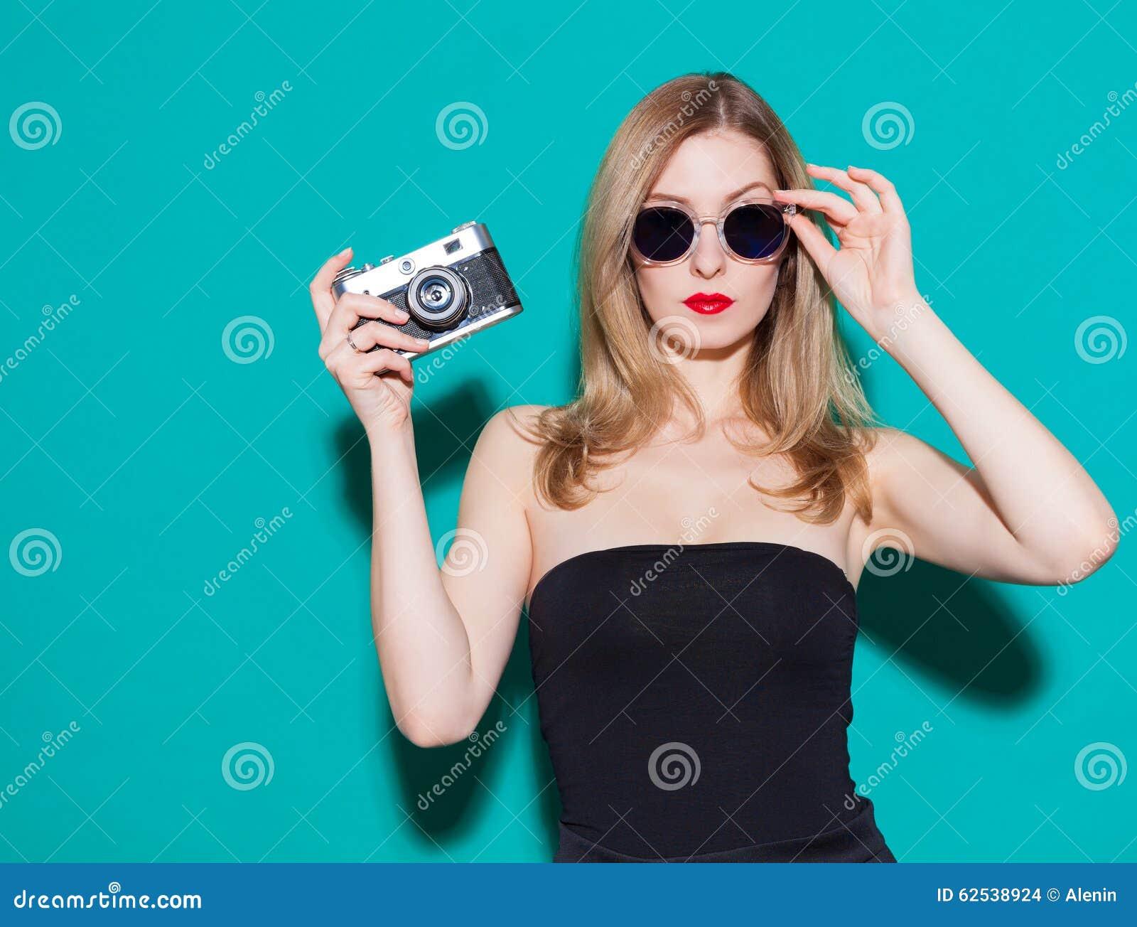 Muchacha de moda hermosa que presenta y que sostiene una cámara del vintage en vestido y gafas de sol negros en el fondo verde en