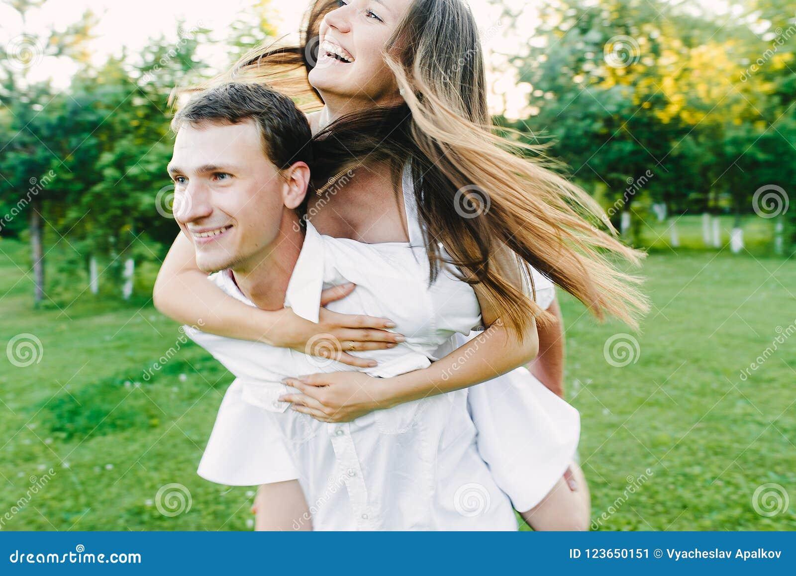 Muchacha de risa feliz que se sienta en su ` s del hombre