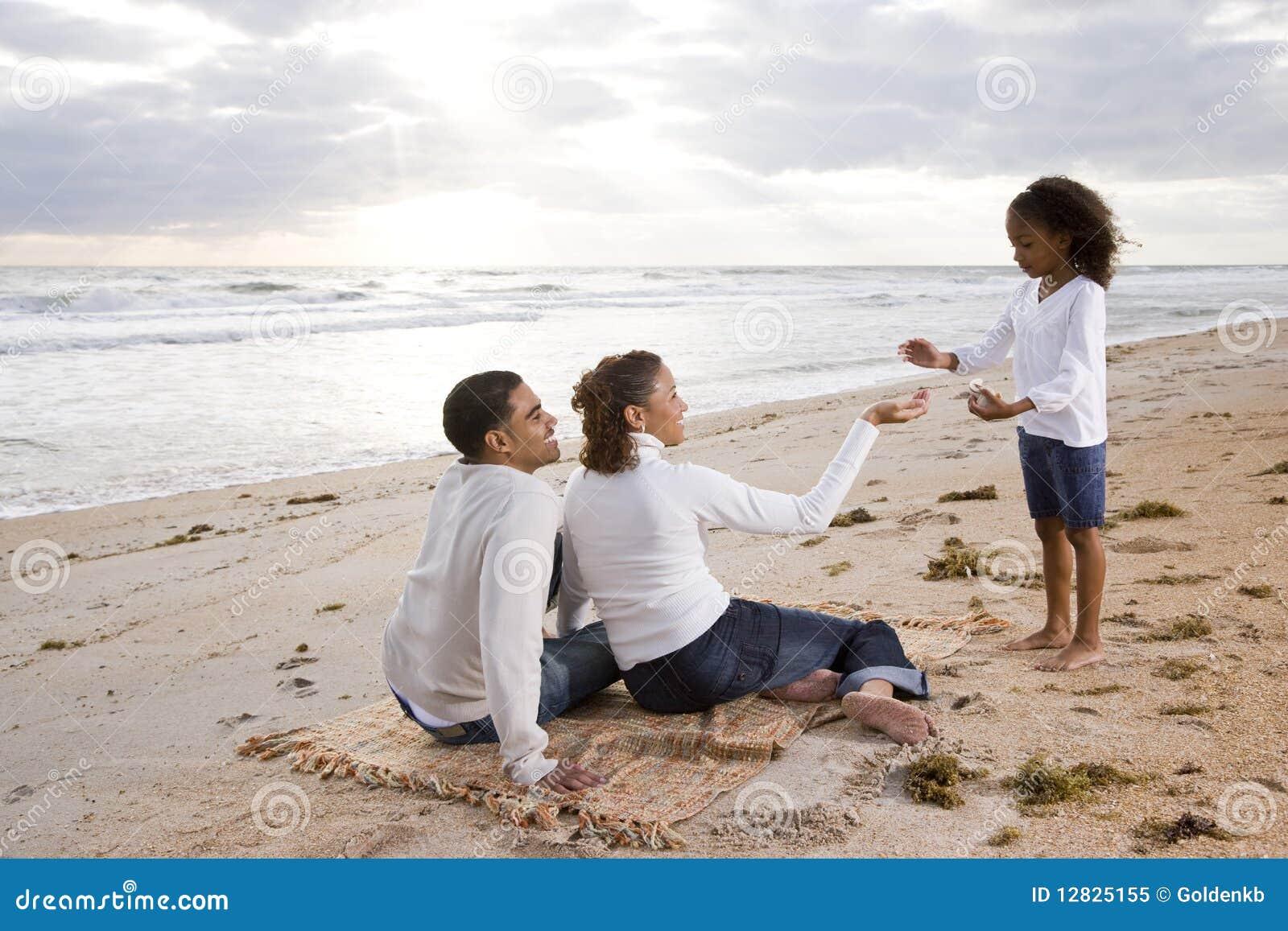 Muchacha del African-American con los padres en la playa