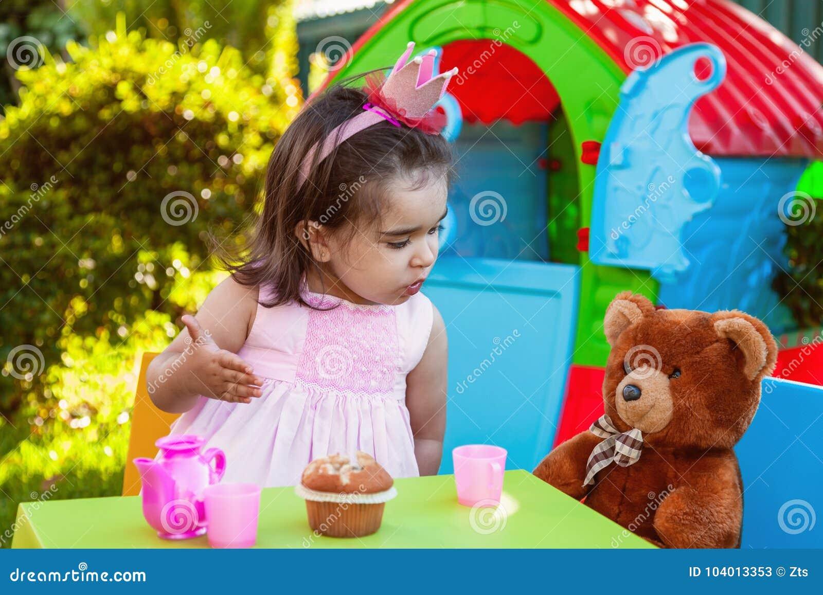 Muchacha del bebé que juega en la fiesta del té al aire libre que habla, charlando o compartiendo a su mejor amigo Teddy Bear