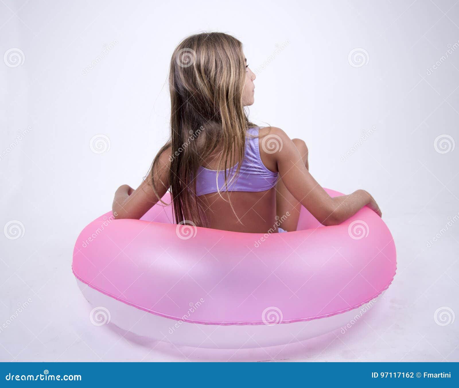 Muchacha del bikini en un flotador en ella detrás