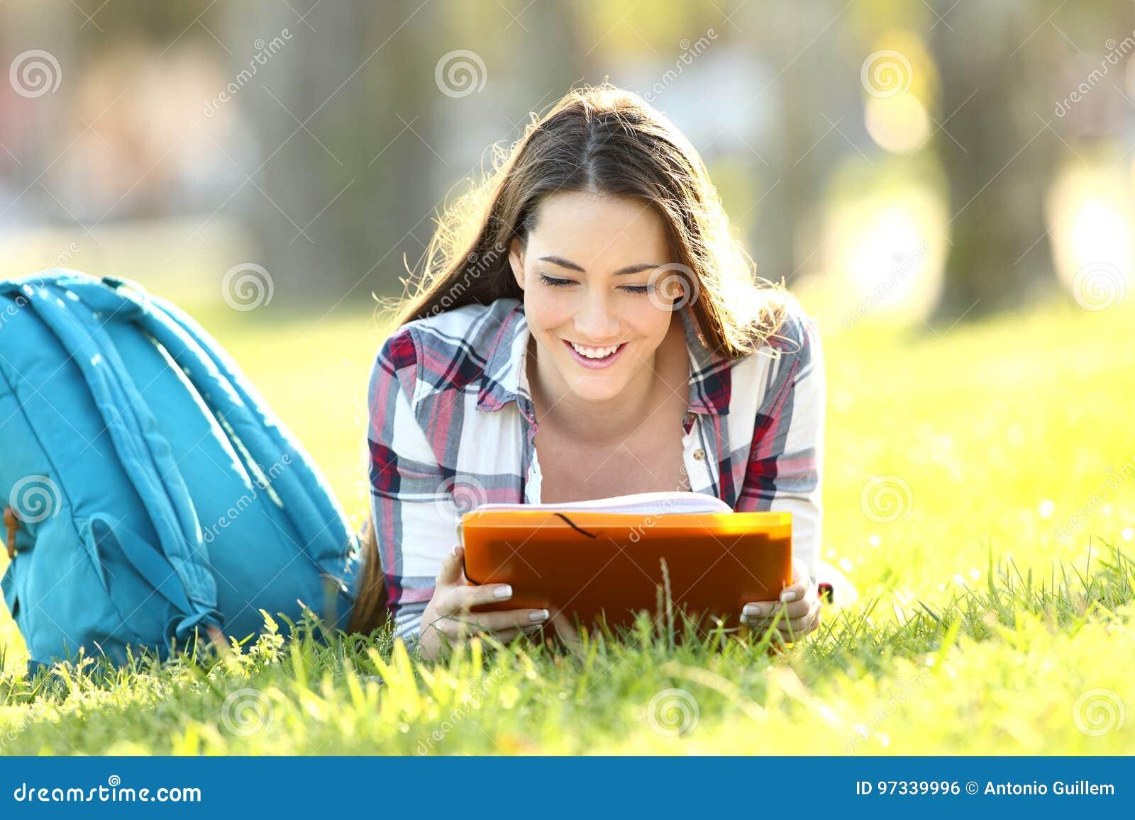 Muchacha del estudiante que aprende notas de la lectura en un campus