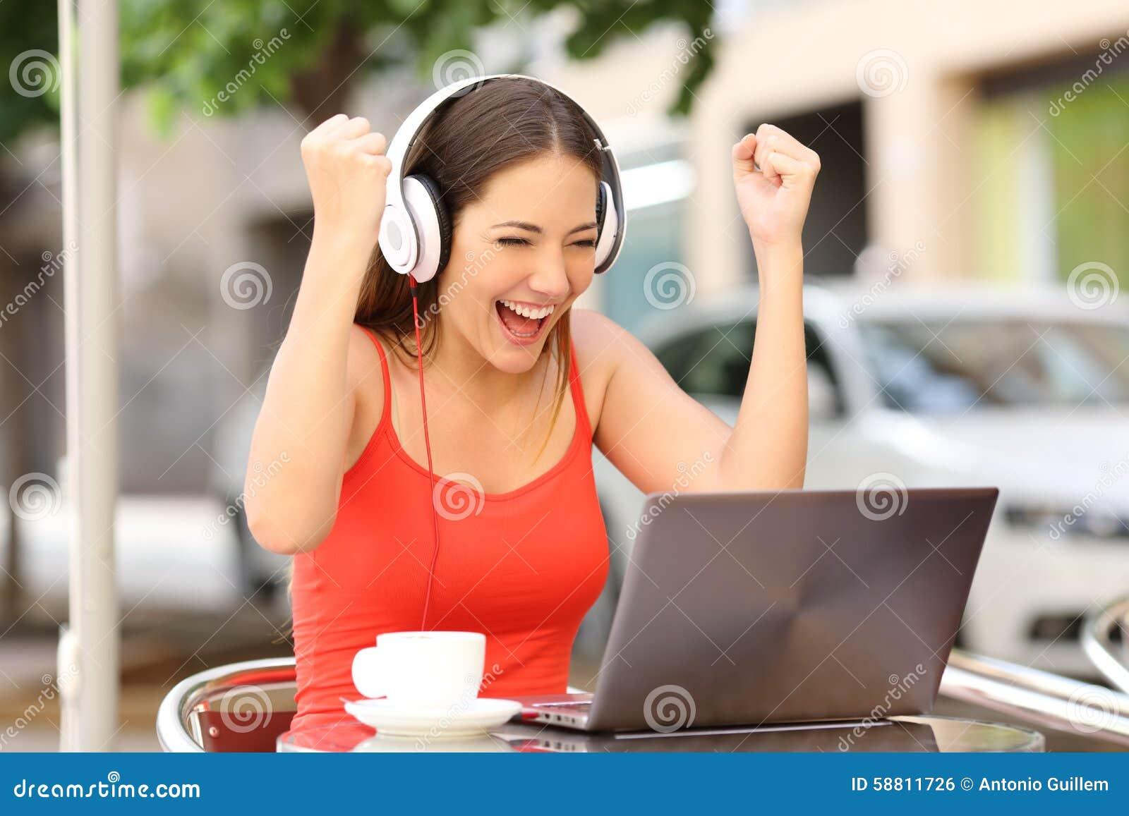 Muchacha del ganador eufórica mirando un ordenador portátil