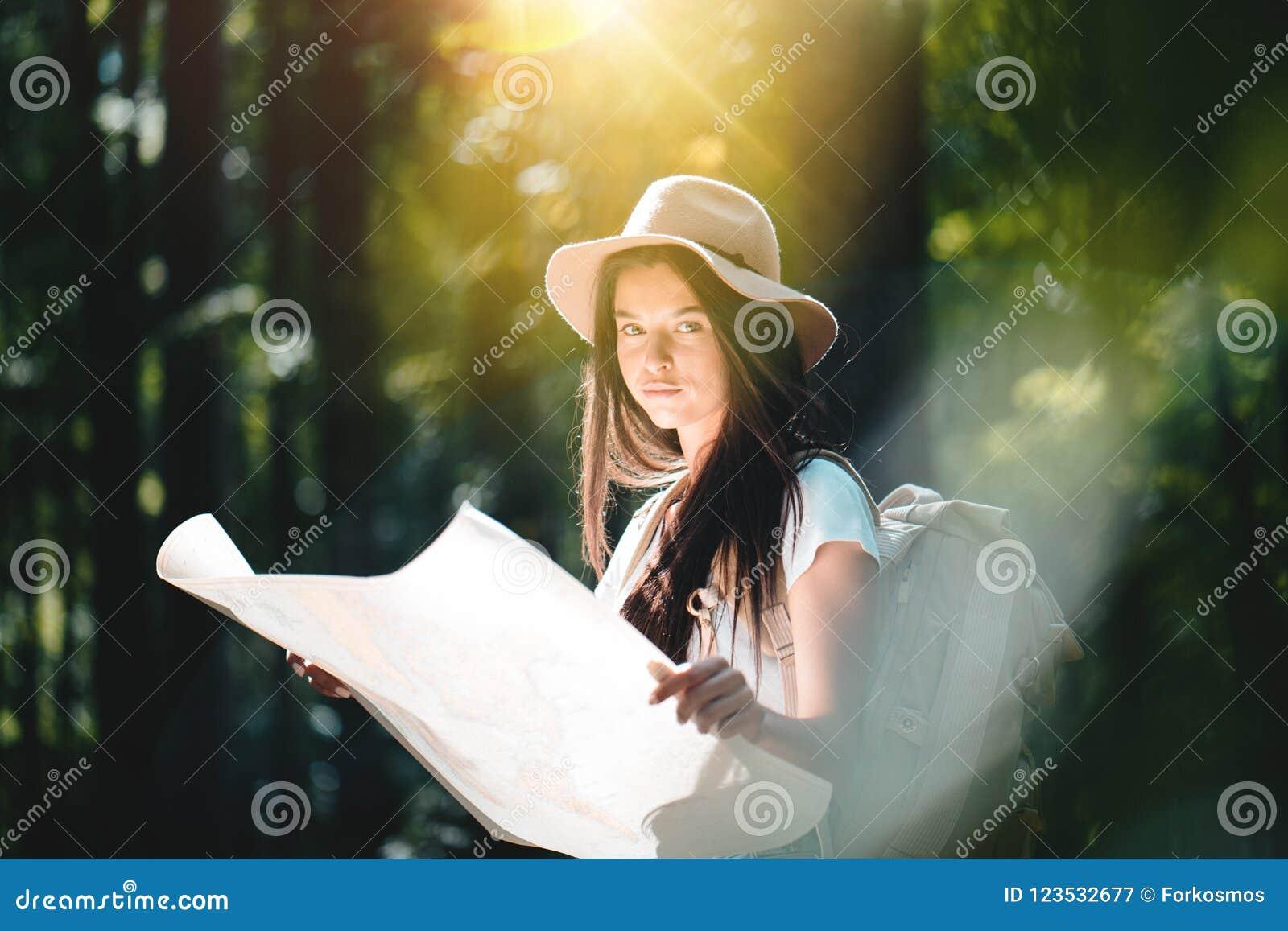 Muchacha del inconformista con la mochila del viaje, y mapa de ubicación en las manos que miran la manera direccional para viajar